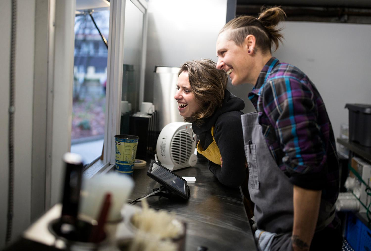 Ande Janousek, right, and Tara Zumpano laugh with customers as they cook up tasty breakfast sandwiches at their Sunny Up food truck. (Sy Bean / Seattle Refined)