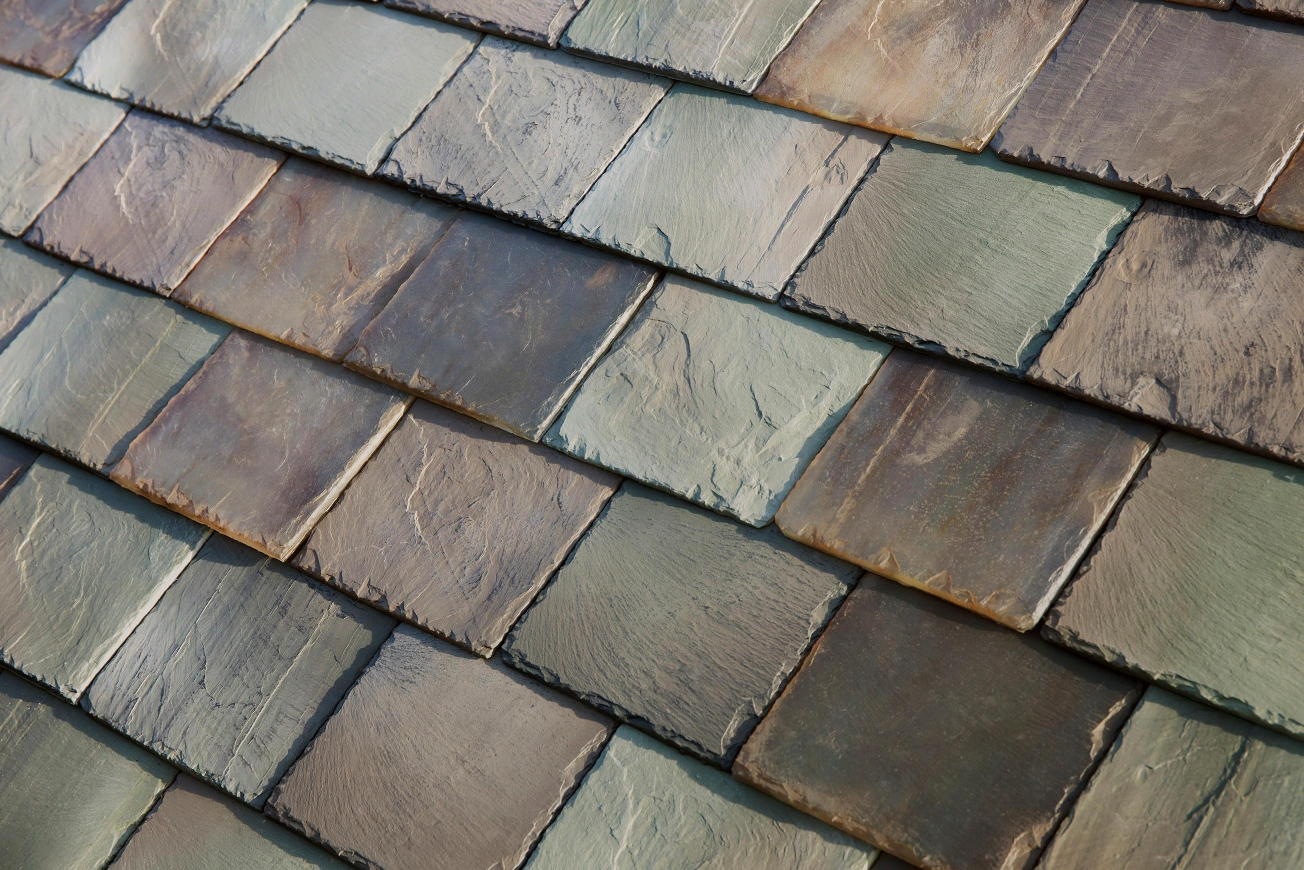 This photo provided by Tesla shows a detail of Tesla's new slate solar roof tiles. As of Wednesday, May 10, 2017, customers worldwide could order a solar roof on Tesla's website. The glass tiles are designed to look like a traditional roof, with options that replicate slate or terracotta tiles. The solar tiles contain photovoltaic cells that are invisible from the street. Installations will begin in June in the U.S., starting with California. Installations outside the U.S. will begin in 2018, the company said. (Courtesy of Tesla via AP)