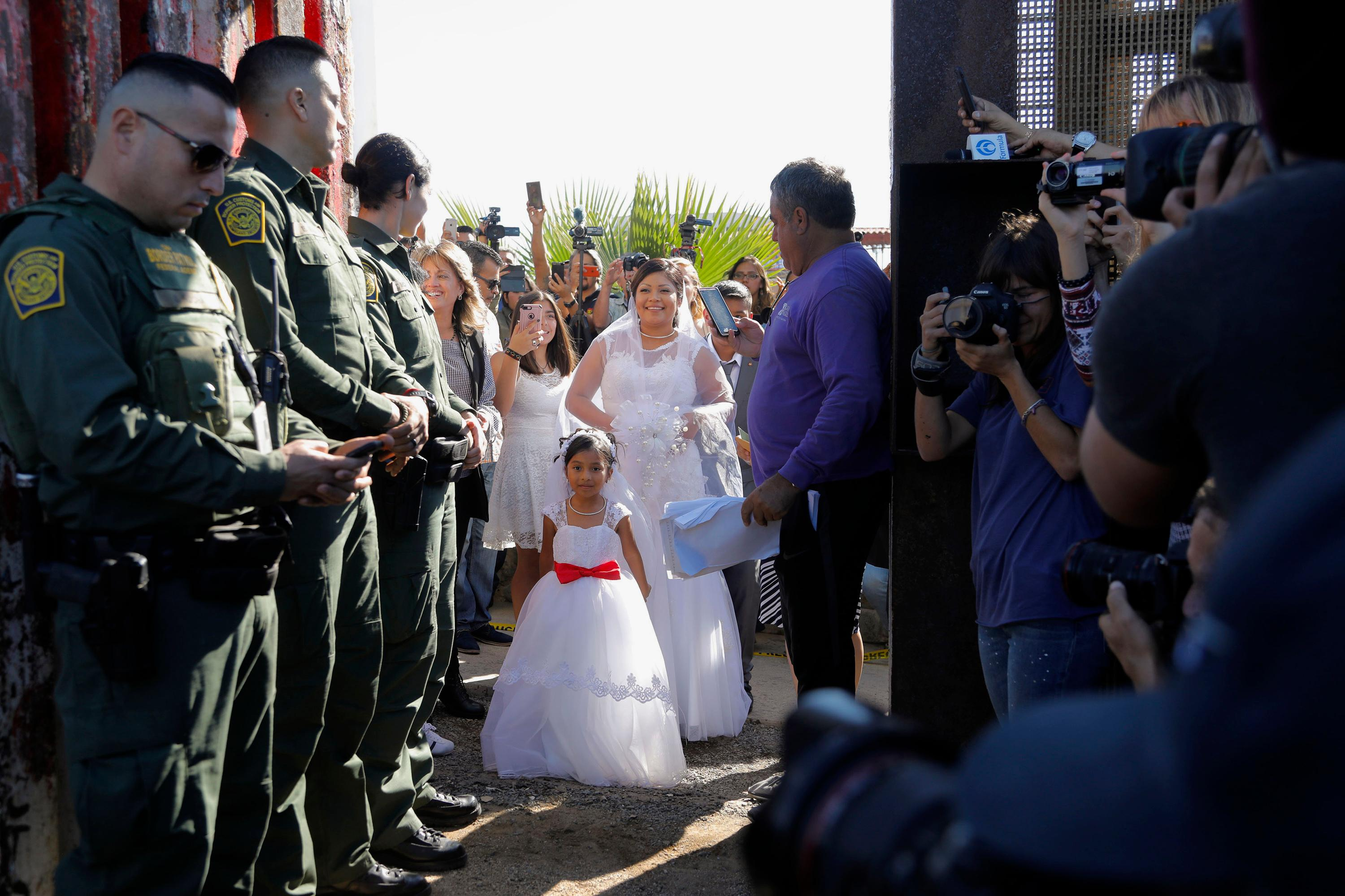 "In this Saturday, Nov. 18, 2017, photo, Evelia Reyes, along with her daughter, watches at the ""Door of Hope"", part of the for the border fence, for her fiance, Brian Houston, of San Diego, to walk up for their wedding in San Diego. The United States man and the Mexican woman wedded Saturday between the doors of a steel border gate that opens for only an hour or so every year. Their wedding in San Diego was the first for an opening of the gate known as the Door of Hope. (Howard Lipin//The San Diego Union-Tribune via AP)"