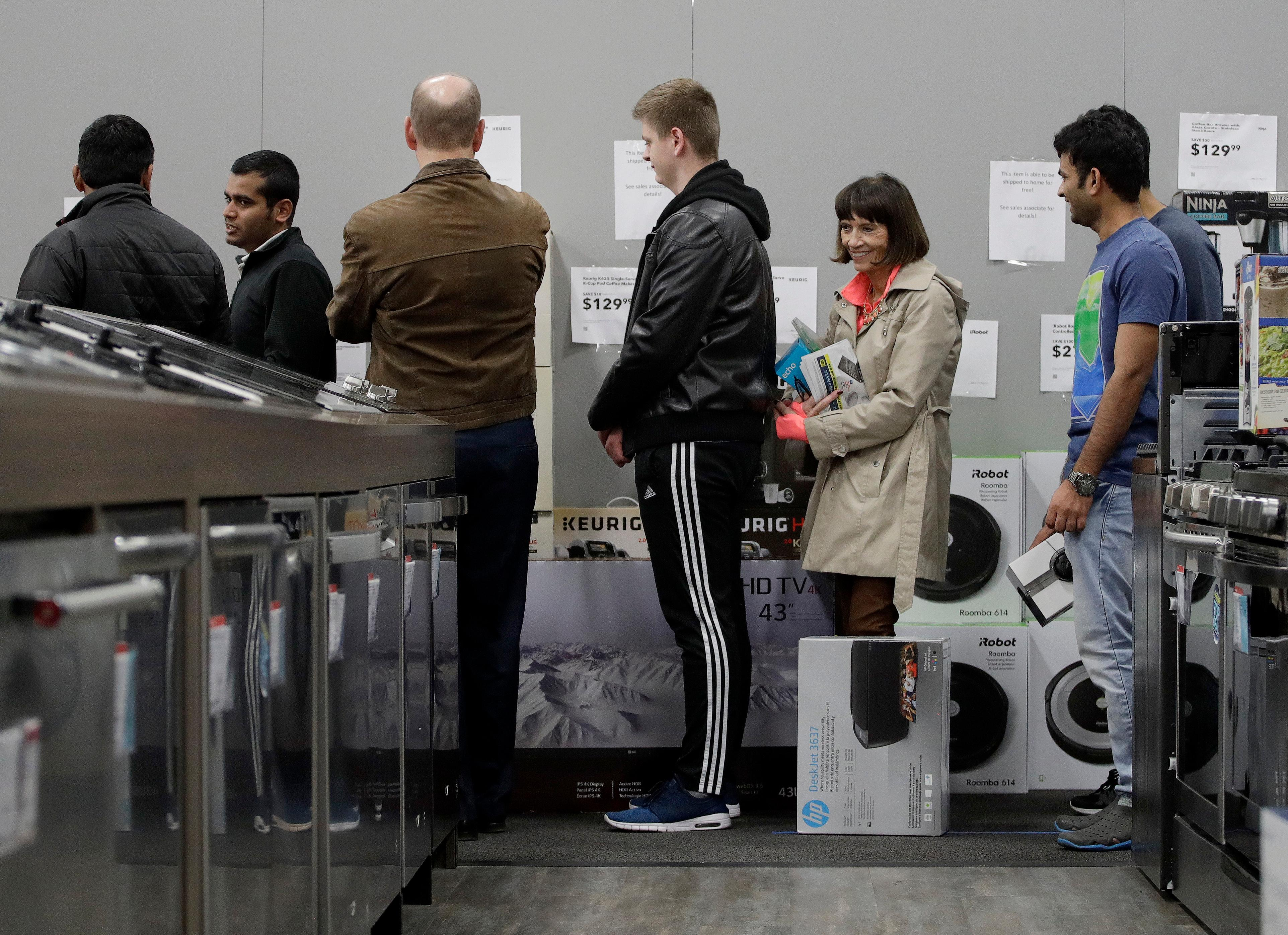 People line up to check out as they shop a Black Friday sale at a Best Buy store on Thanksgiving Day, Thursday, Nov. 23, 2017, in Overland Park, Kan. Shoppers are hitting the stores on Thanksgiving as retailers under pressure look for ways to poach shoppers from their rivals. (AP Photo/Charlie Riedel)