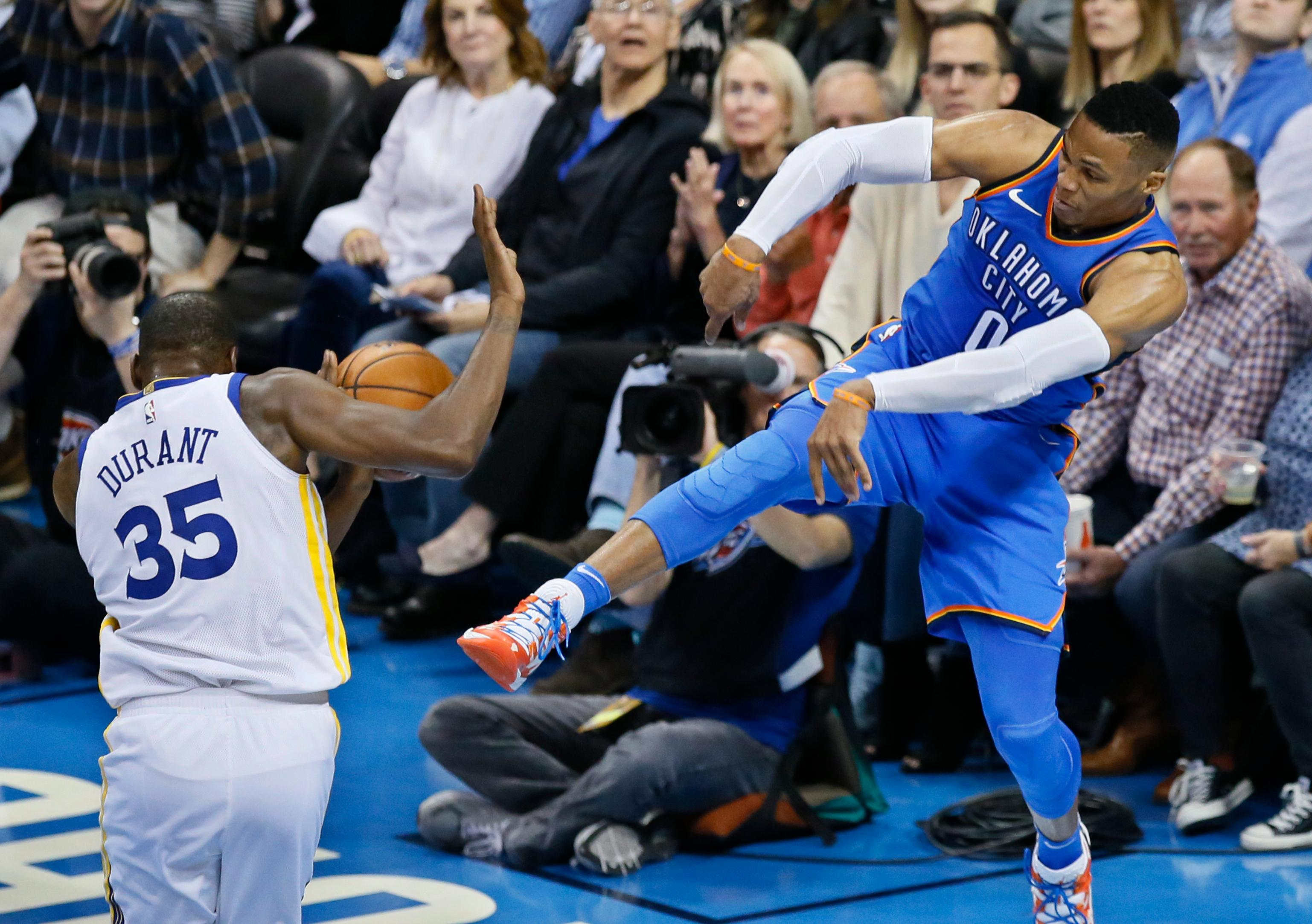 Oklahoma City Thunder guard Russell Westbrook (0) attempts to throw the ball off of Golden State Warriors forward Kevin Durant (35) during the second quarter of an NBA basketball game in Oklahoma City, Wednesday, Nov. 22, 2017. (AP Photo/Sue Ogrocki)