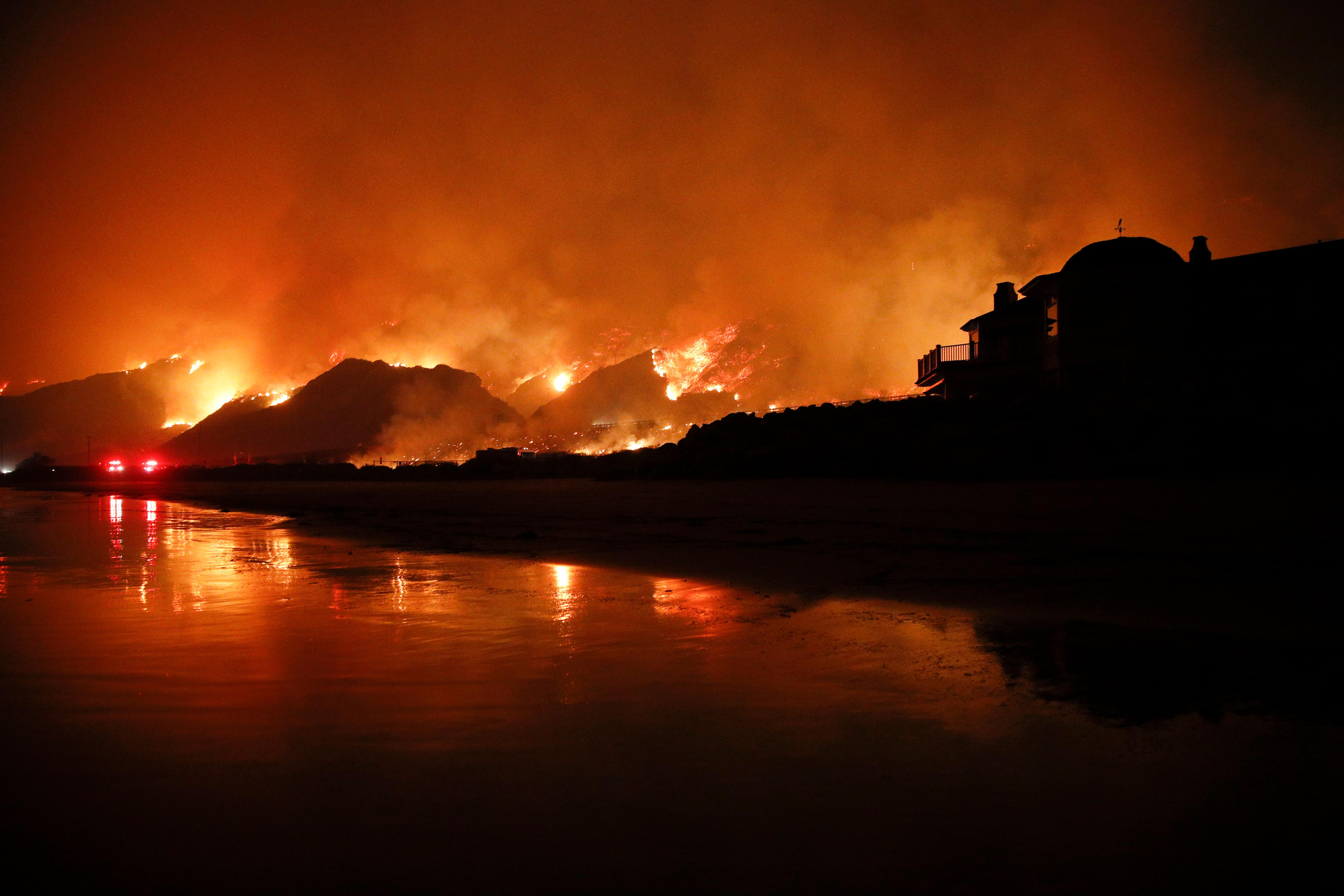 A wildfire burns along the 101 Freeway Tuesday, Dec. 5, 2017, in Ventura, Calif. Raked by ferocious Santa Ana winds, explosive wildfires northwest of Los Angeles and in the city's foothills burned a psychiatric hospital and scores of homes and other structures Tuesday and forced the evacuation of tens of thousands of people. (AP Photo/Jae C. Hong)