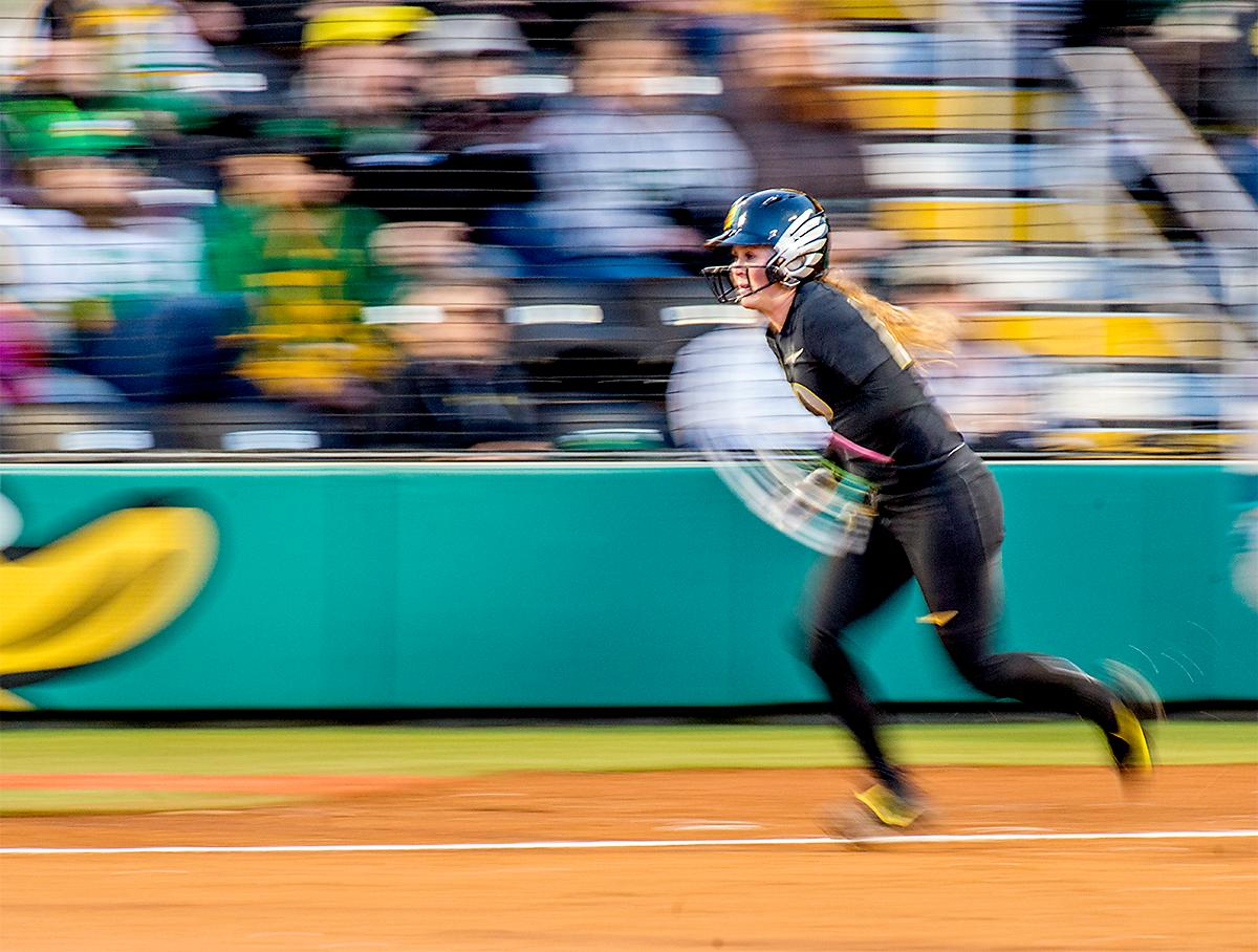 The Duck's Jenna Lilley (#00) takes off running for first base. In Game Two of a three-game series, the University of Oregon Ducks softball team defeated the University of Washington Huskies 4-1 Friday night in Jane Sanders Stadium. Danica Mercado (#2), Alexis Mack (#10) and Mia Camuso (#7) all scored in the win, Mack twice. The Ducks play the Huskies for the tie breaker on Saturday with the first pitch at noon. Photo by August Frank, Oregon News Lab