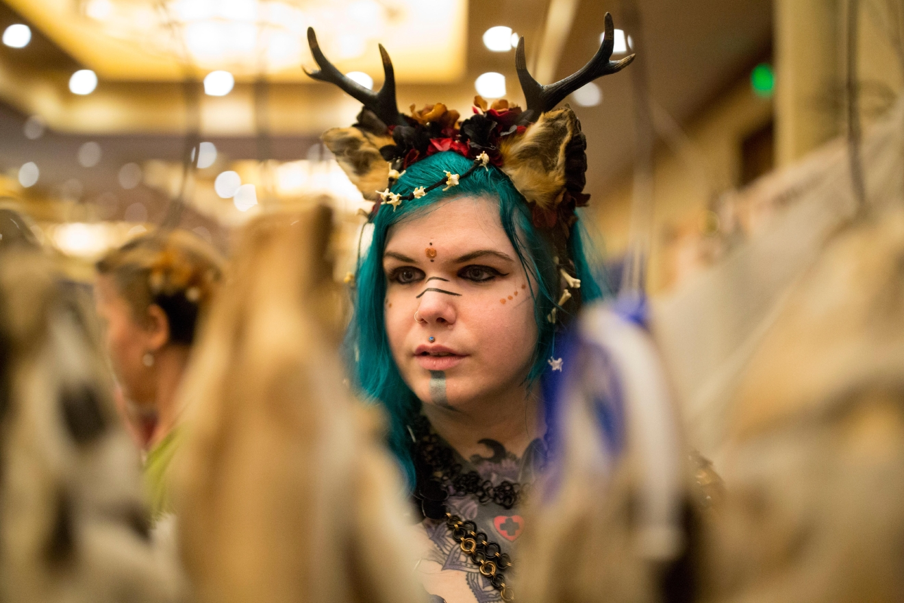 Fremont resident Chivahn Wilkens browses through fox furs at a vendors booth at Mythicworlds Convention and Masquerades. Wilkens dressed as a viking witch, and says she specializes in crafting drinking horns and head dresses. (Sy Bean / Seattle Refined)