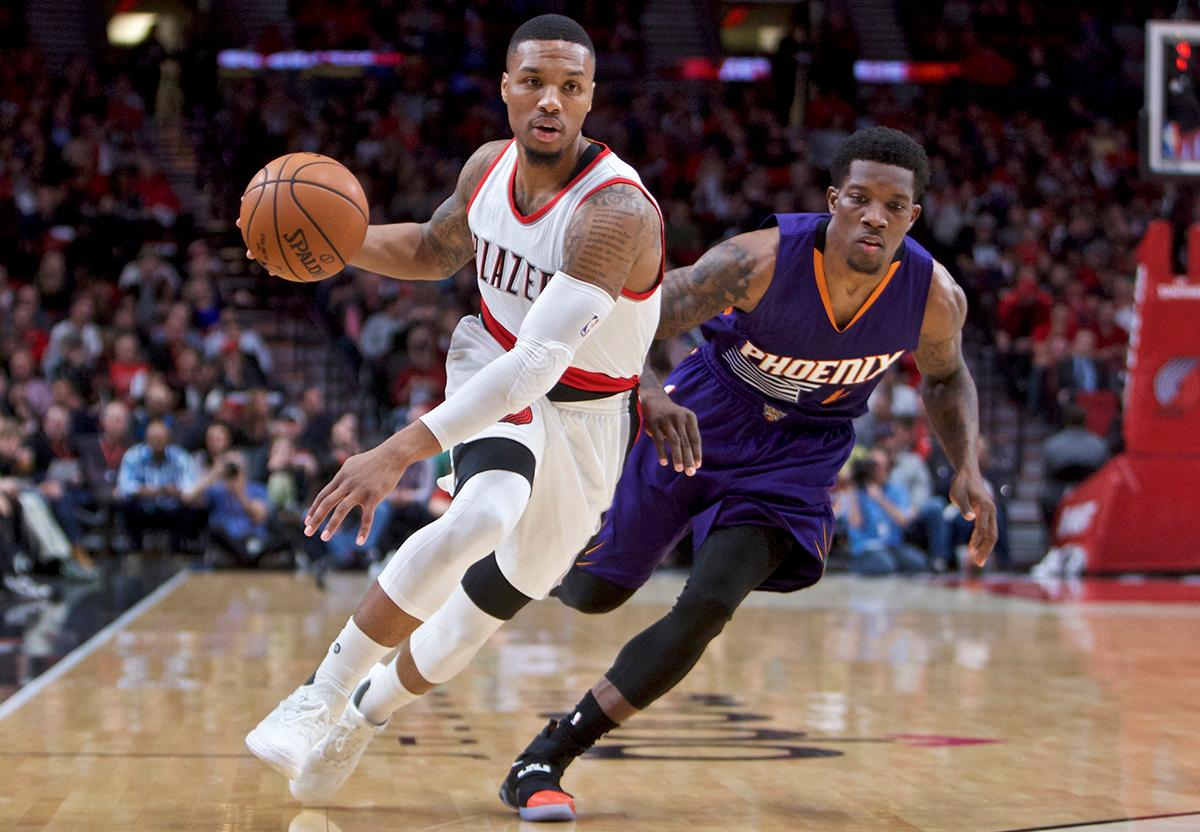 Portland Trail Blazers guard Damian Lillard, left, dribbles around Phoenix Suns guard Eric Bledsoe during the first half of an NBA basketball game in Portland, Ore., Tuesday, Nov. 8, 2016. (AP Photo/Craig Mitchelldyer)