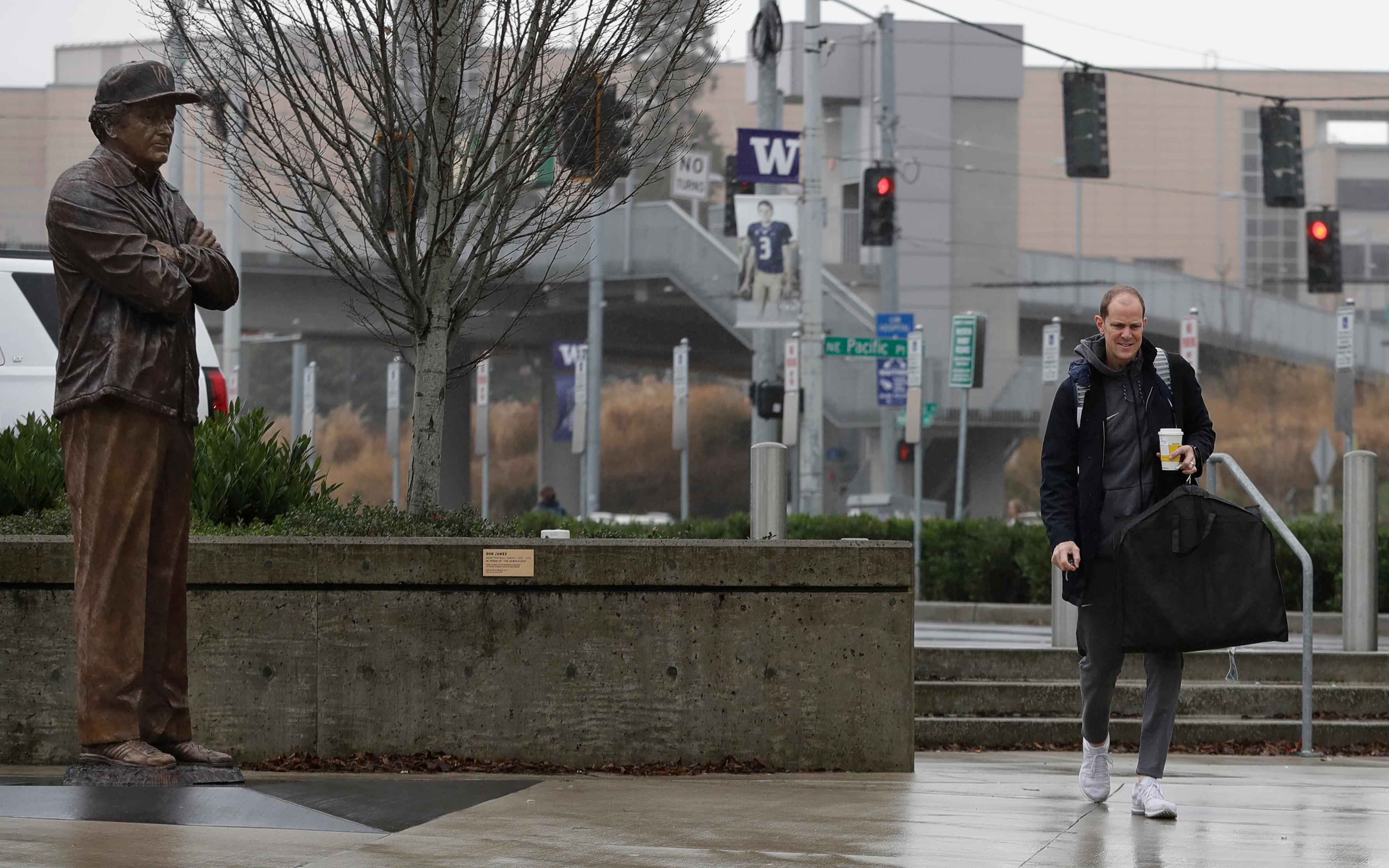In this Sunday, Jan. 28, 2018 photo,  Washington head coach Mike Hopkins walks past the statue of legendary Washington football coach Don James as he arrives on campus before an NCAA college basketball game against Washington State in Seattle. One of the most surprising stories in college basketball is what Hopkins is doing in his first season at Washington and how the Huskies are in the conversation for an NCAA bid entering February. (AP Photo/Ted S. Warren)