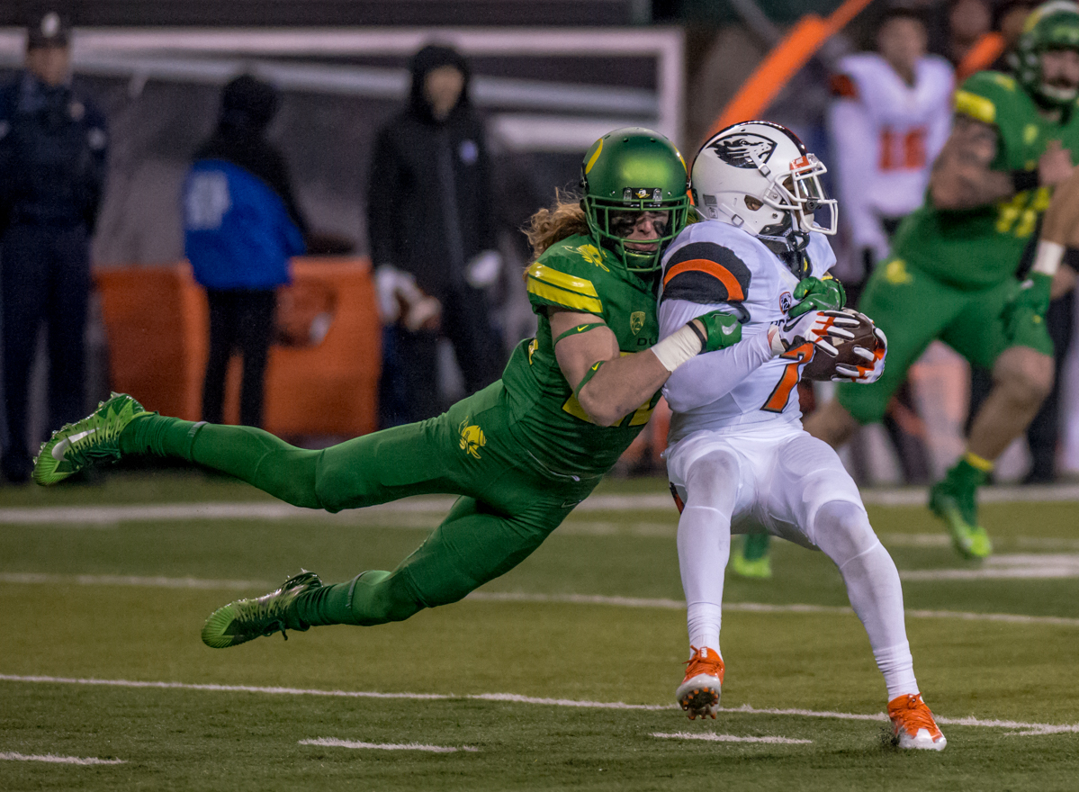 Oregon defensive player Brenden Schooler (#86) takes down Oregon State wide receiver Xavier Hawkins (#7). The Oregon Ducks defeated the Oregon State Beavers 69 to 10 in the 121st Civil War game at Autzen Stadium in Eugene, Ore. on Saturday November 25, 2017. Photo by Ben Lonergan, Oregon News Lab
