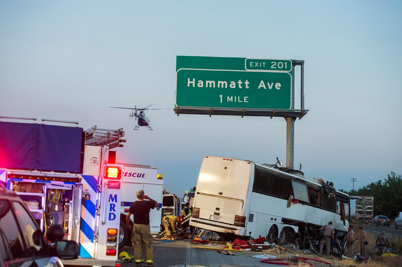 Rescue crews respond to the scene of a charter bus crash on northbound Highway 99 between Atwater and Livingston, Calif., Tuesday, Aug. 2, 2016. The bus veered off the central California freeway before dawn Tuesday and struck a pole that sliced the vehicle nearly in half, authorities said. (Andrew Kuhn/Merced Sun-Star via AP)