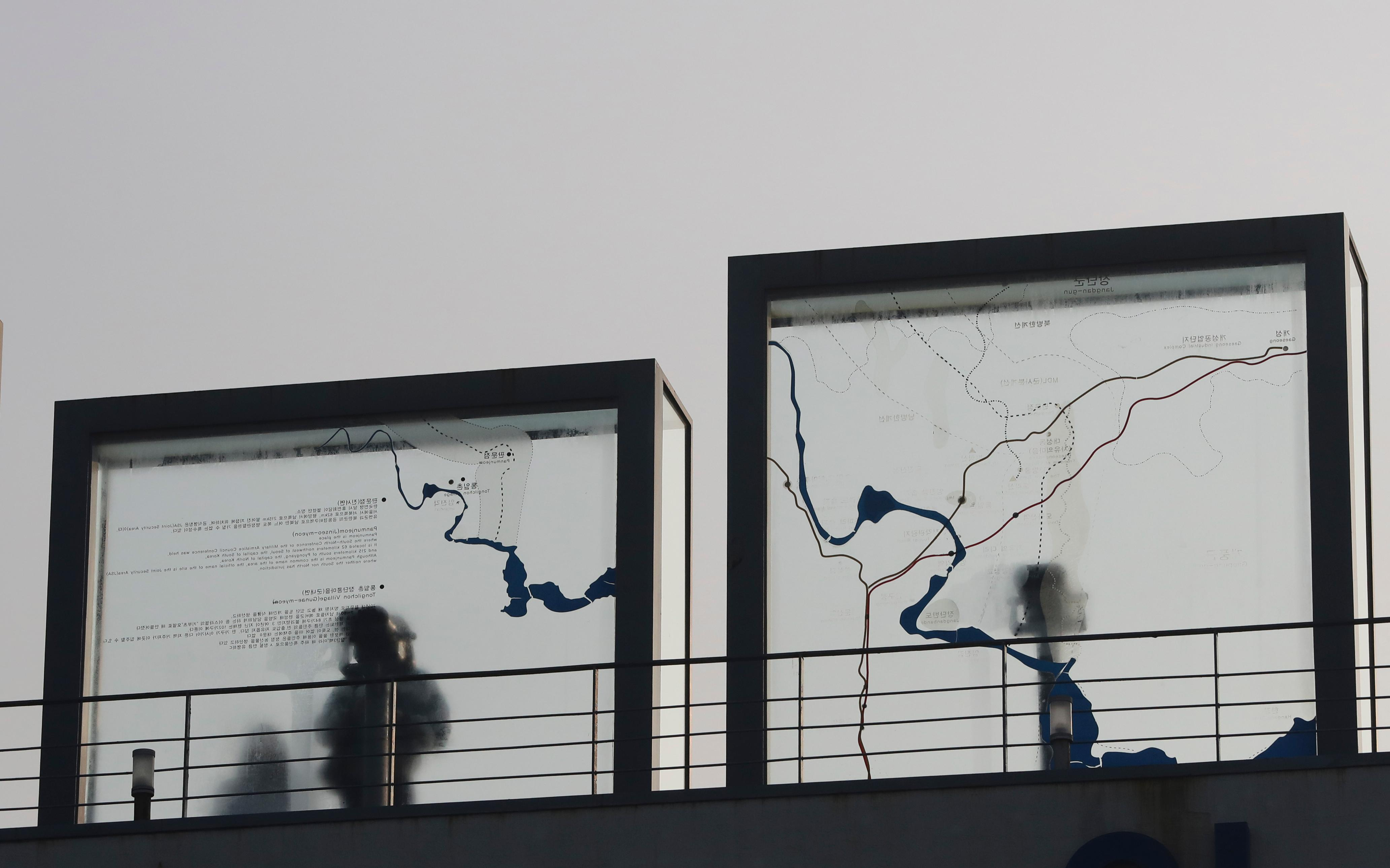 A visitor watches the north side through the glass showing a map of Panmunjom where the place for two Koreas meeting, at the Imjingak Pavilion in Paju, South Korea, Wednesday, Jan. 17, 2018. The two Koreas are meeting Wednesday for the third time in about 10 days to continue their discussions on Olympics cooperation, days ahead of talks with the IOC on North Korean participation in the upcoming Winter Games in the South. (AP Photo/Lee Jin-man)