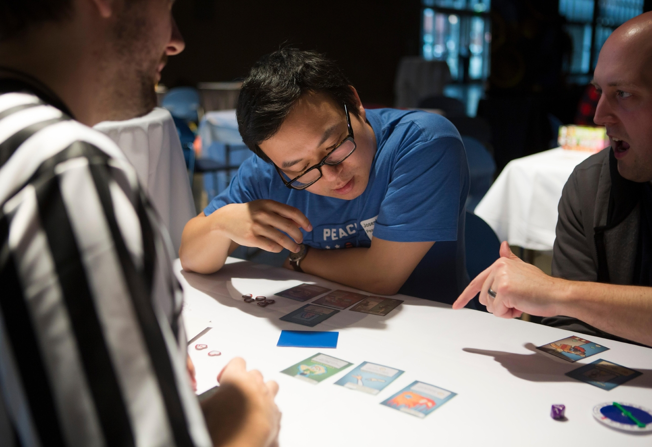 Joseph Chen follows along as he learns the board game titled Beatdown: at the 6th annual Geekwire Bash at the CenturyLink Event Center. (Sy Bean / Seattle Refined)