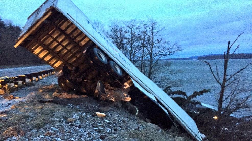 Semi slides through highway guard rail tips off steep