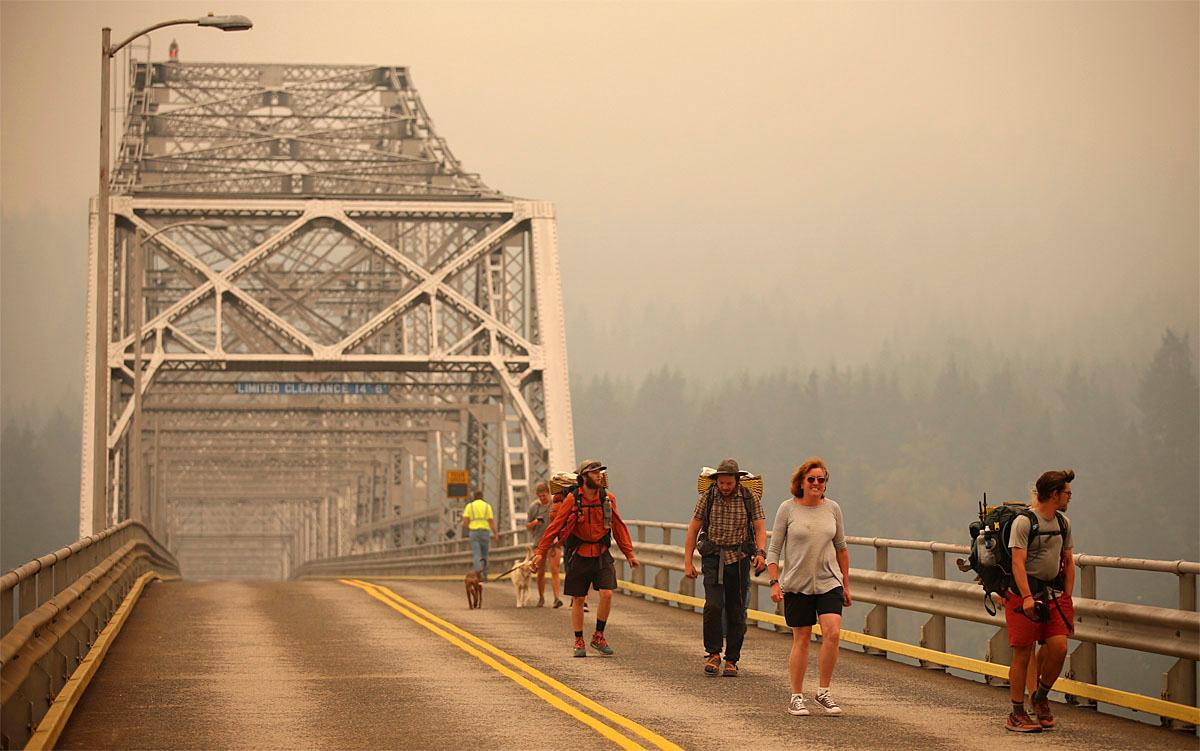 Pedestrians walk off the Bridge of the Gods, which spans the Columbia River between Washington and Oregon states, as smoke from the Eagle Creek wildfire obscures the Oregon hills in the background near Stevenson, Wash., Wednesday, Sept. 6, 2017. The Eagle Creek fire continues to burn on the Oregon side of the river near the town of Cascade Locks, Ore. Officials closed the bridge to pedestrians and onlookers after this photo was taken. (AP Photo/Randy L. Rasmussen)