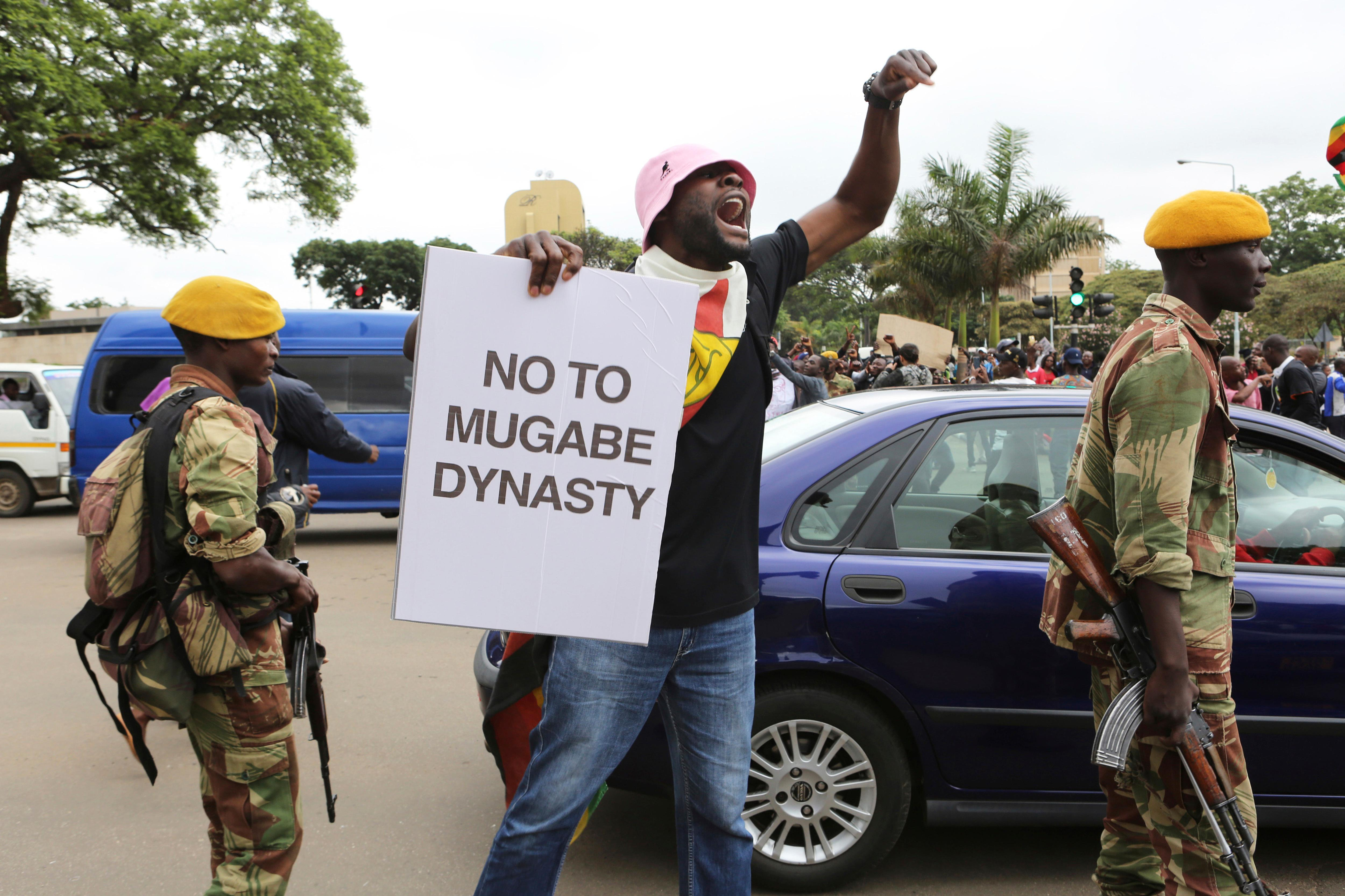 A marcher makes a point as euphoric crowds march on the streets Saturday, Nov. 18, 2017, in Harare, Zimbabwe, demanding the departure of President Robert Mugabe. Zimbabweans giddy with joy raced through intersections, raising their arms in triumph. (AP Photo/Tsvangirayi Mukwazhi)