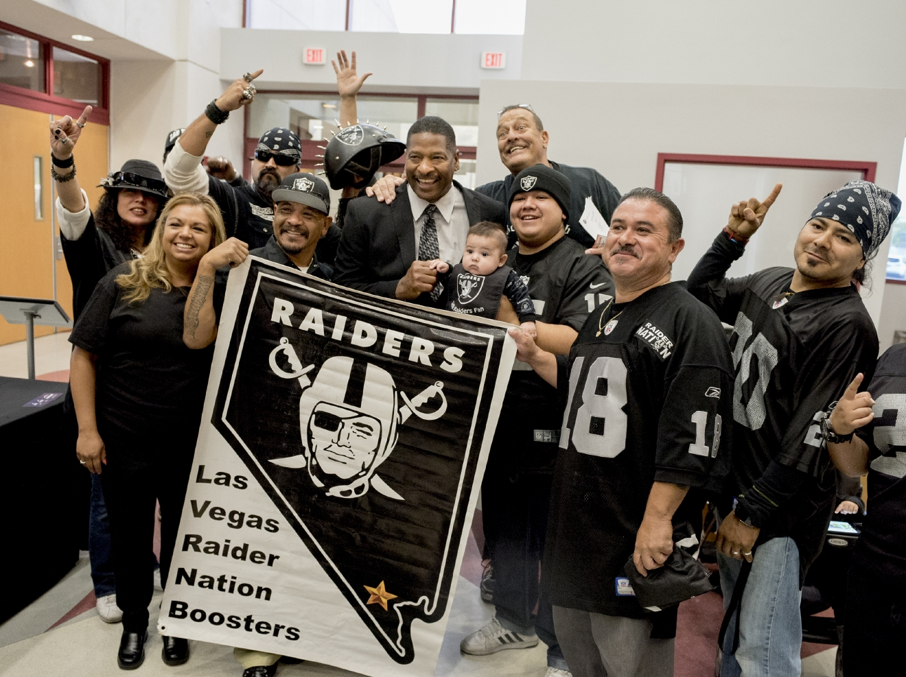 Napoleon McCallum, center, former Los Angeles Raiders running back, is surrounded by local members of the Raiders Nation before a meeting of the Southern Nevada Tourism Infrastructure Committee at the Stan Fulton Building, UNLV on Thursday, April 28, 2016. The committee was to hear arguments to bring the Oakland Raiders to Las Vegas and build a domed stadium for them near the Strip.  (Mark Damon/Las Vegas News Bureau)