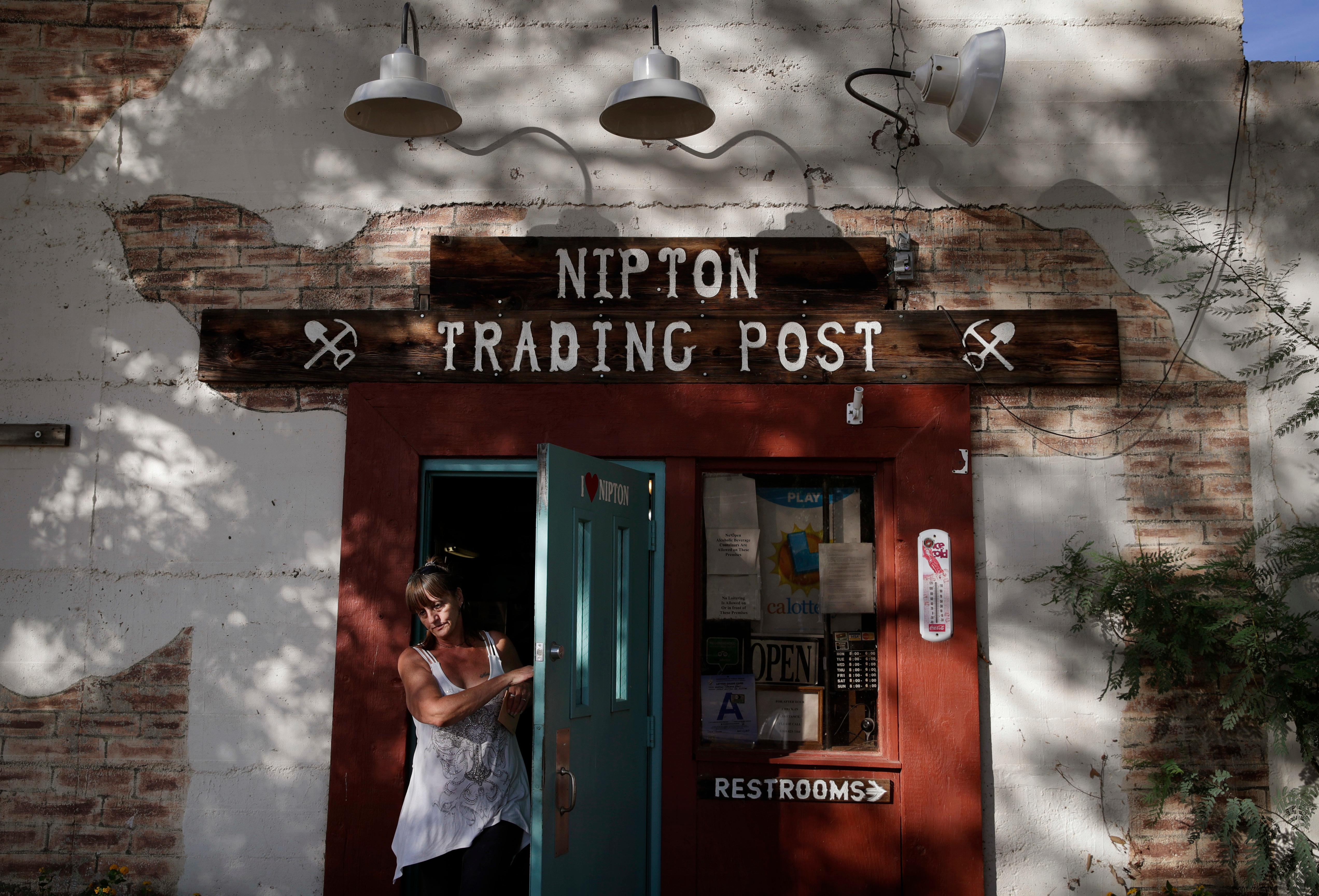 A woman leaves the Nipton Trading Post, Thursday, Aug. 3, 2017, in Nipton, Calif. American Green Inc., one of the nation's largest cannabis companies, announced it has bought the entire 80 acre California desert town of Nipton. (AP Photo/John Locher)