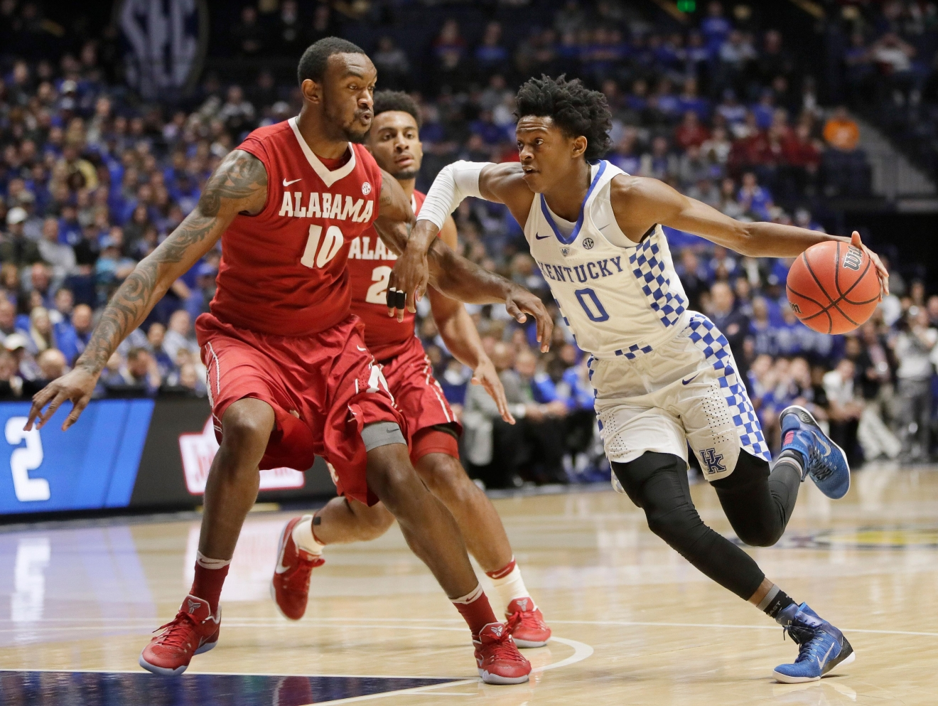 Kentucky guard De'Aaron Fox (0) drives against Alabama forward Jimmie Taylor (10) in the first half of an NCAA college basketball game in the semifinals of the Southeastern Conference tournament Saturday, March 11, 2017, in Nashville, Tenn. (AP Photo/Wade Payne)