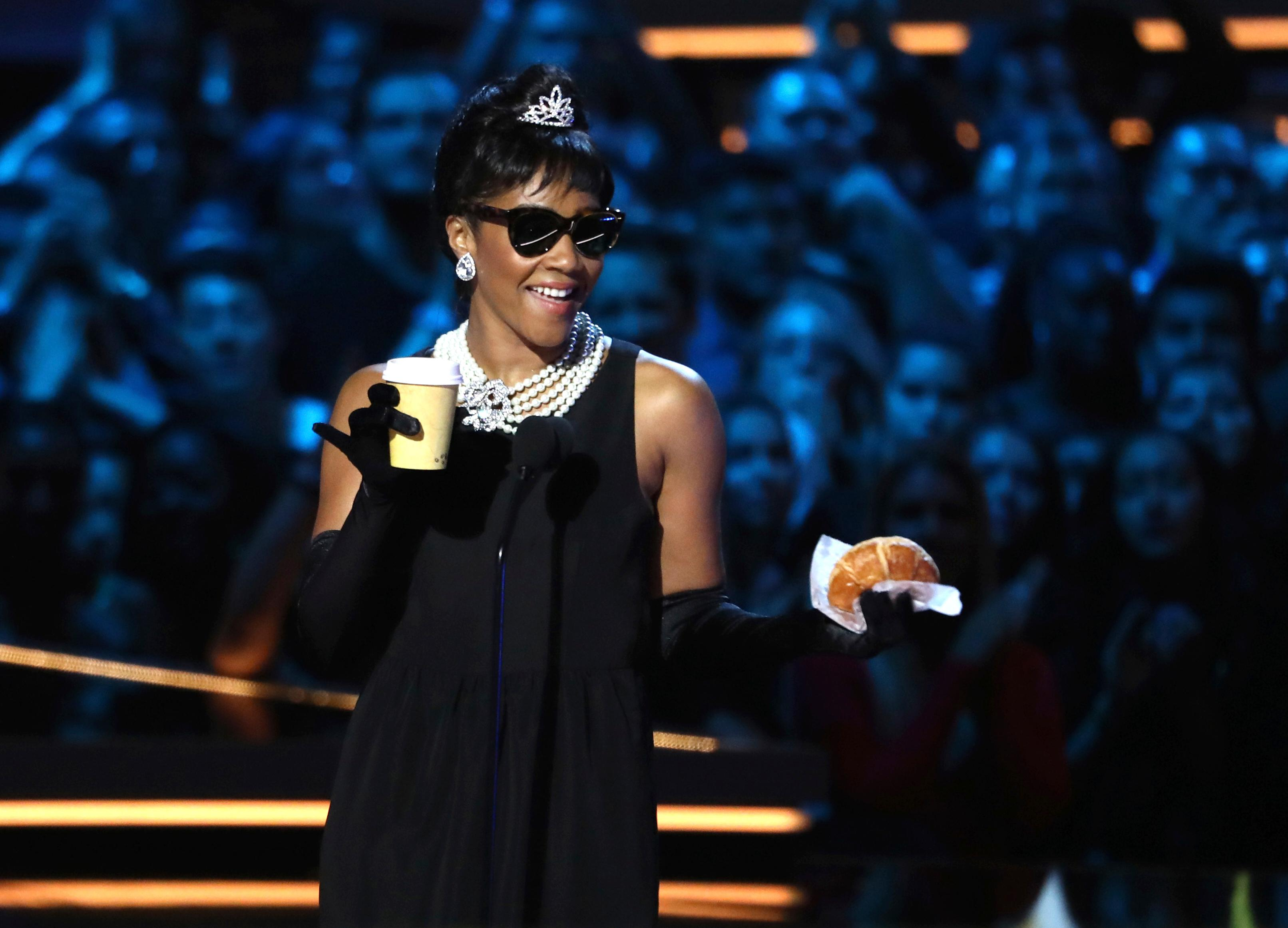"In this Saturday, June 16, 2018, photo, host Tiffany Haddish, dressed up as Holly Golightly from ""Breakfast at Tiffany's,"" speaks at the MTV Movie and TV Awards at the Barker Hangar in Santa Monica, Calif. (Photo by Matt Sayles/Invision/AP)"