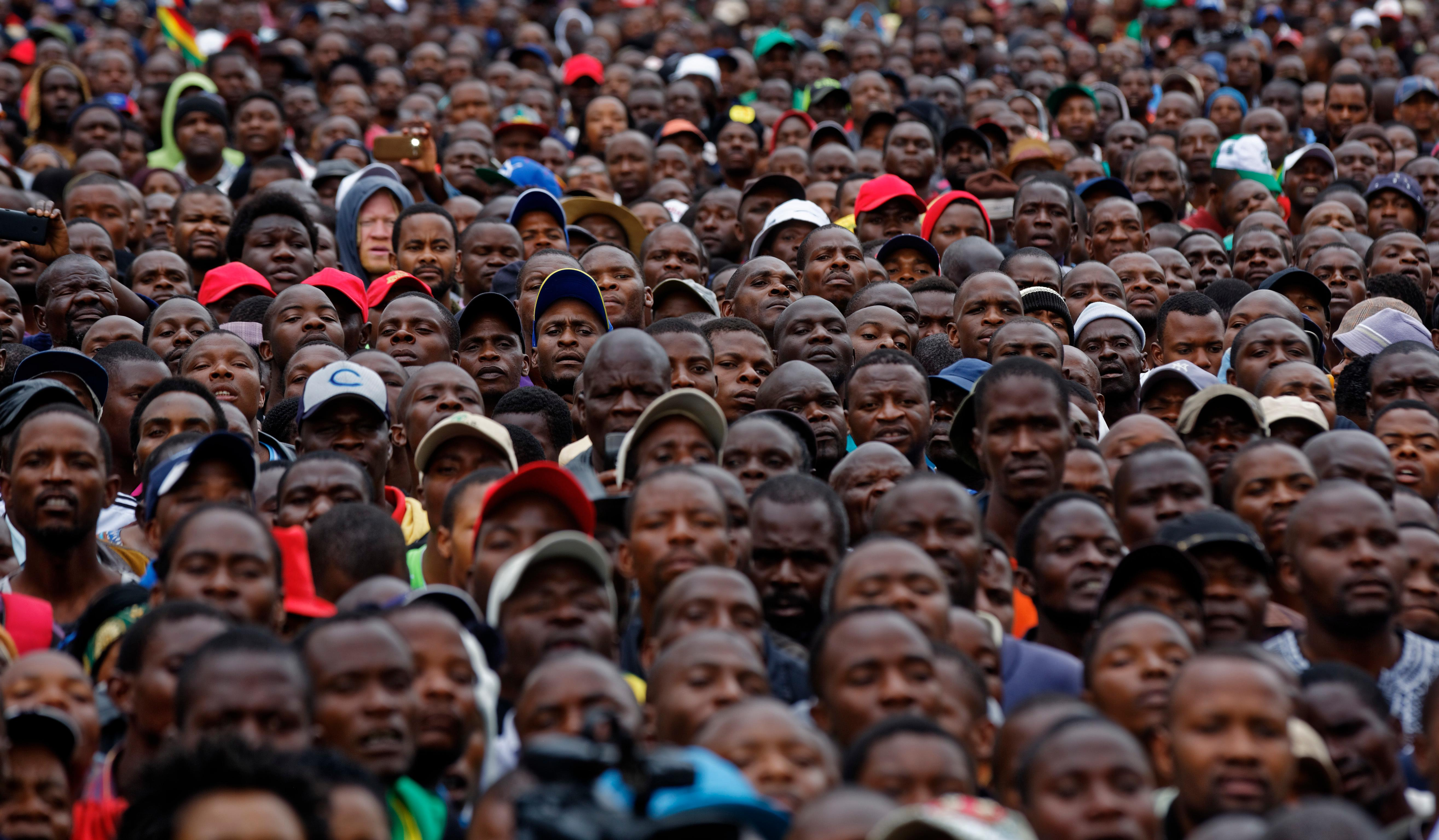 Protesters gather at a demonstration of tens of thousands at Zimbabwe Grounds in Harare, Zimbabwe Saturday, Nov. 18, 2017. Opponents of Mugabe are demonstrating for the ouster of the 93-year-old leader who is virtually powerless and deserted by most of his allies. (AP Photo/Ben Curtis)