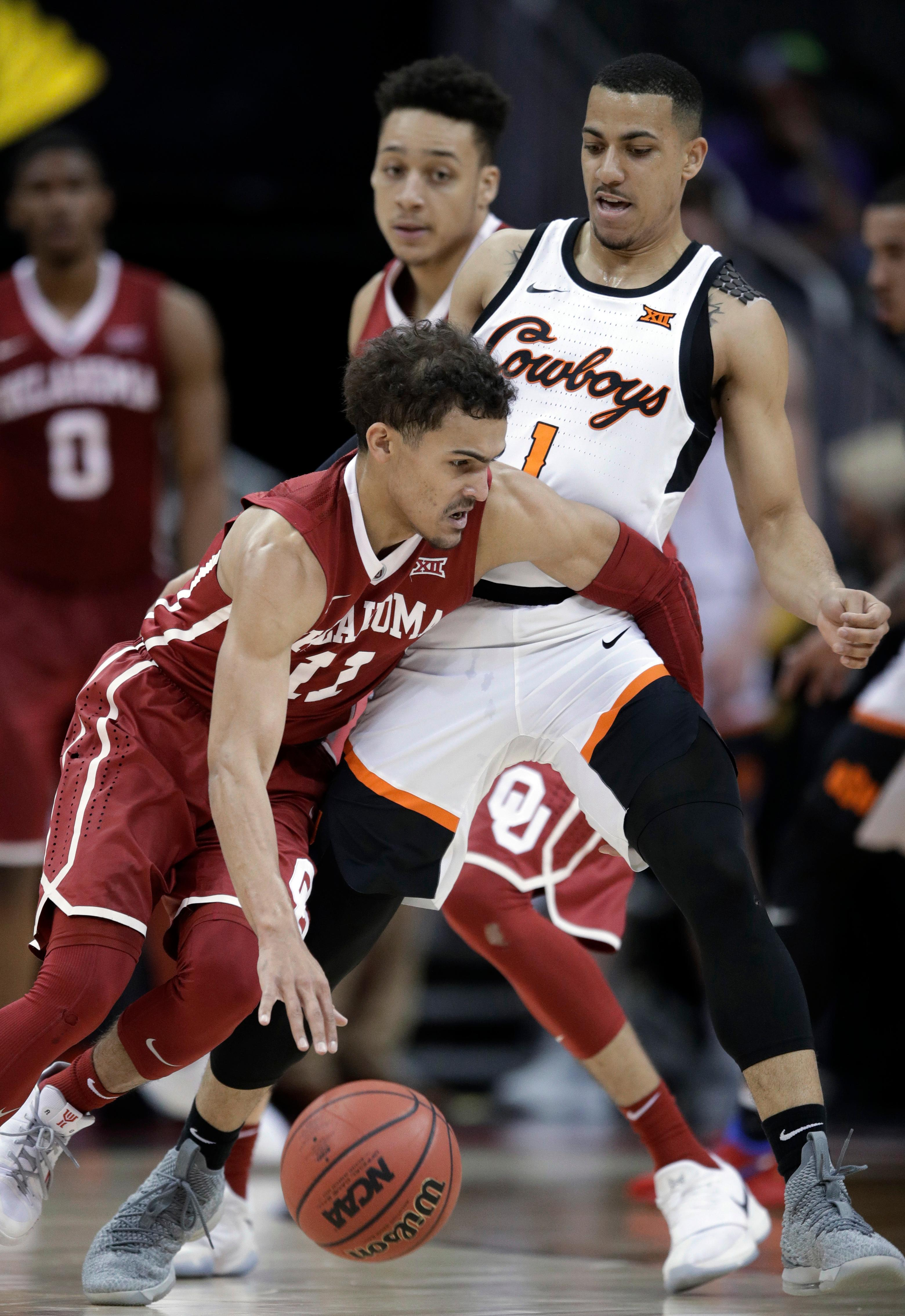 Oklahoma guard Trae Young (11) works around Oklahoma State guard Kendall Smith (1) during the first half of an NCAA college basketball game in first round of the Big 12 men's tournament in Kansas City, Mo., Wednesday, March 7, 2018. (AP Photo/Orlin Wagner)