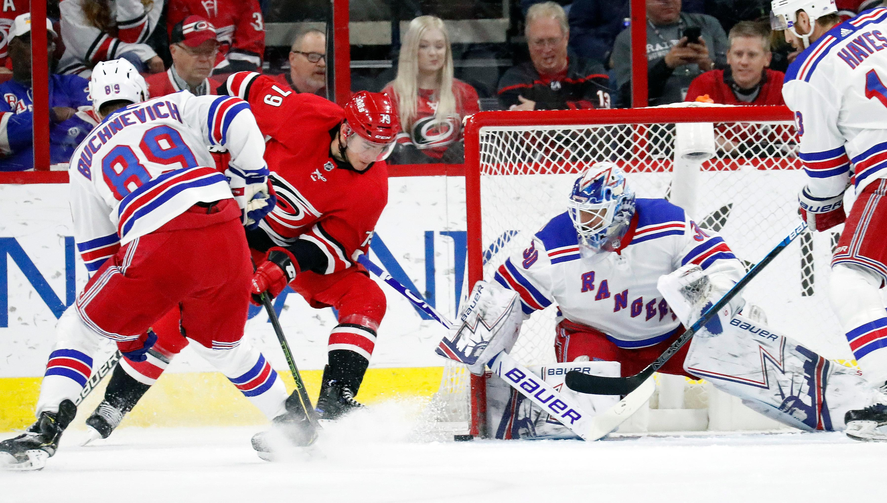 Carolina Hurricanes' Micheal Ferland (79) is defended by New York Rangers' Pavel Buchnevich (89) from Russia and Henrik Lundqvist (30) of Sweden during the first period of an NHL hockey game in Raleigh, N.C., Tuesday, Feb. 19, 2019. (AP Photo/Chris Seward)
