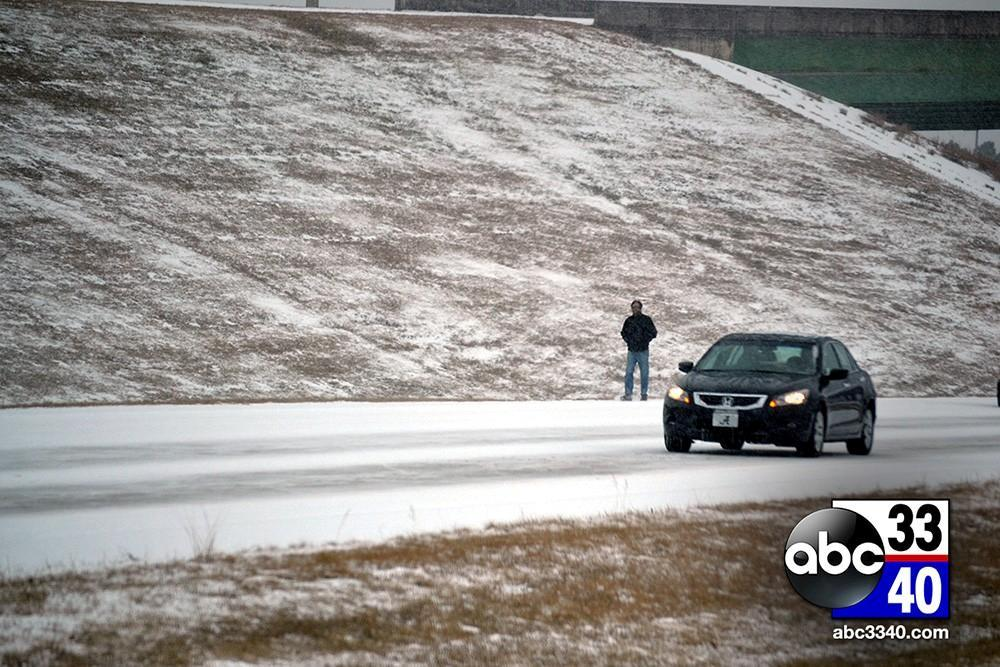 A man walks along Interstate 459 East after becoming stranded during a winter storm in Alabama, Tuesday, January 28, 2014.