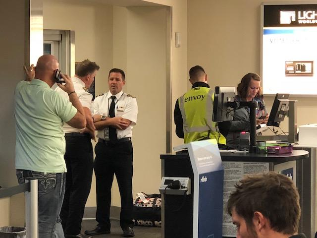 Photo courtesy Kathryn Janicek{ } The pilots of an American Airlines flight from Phoenix to Medford Sunday chat after passengers were quickly evacuated near the airport fire station.