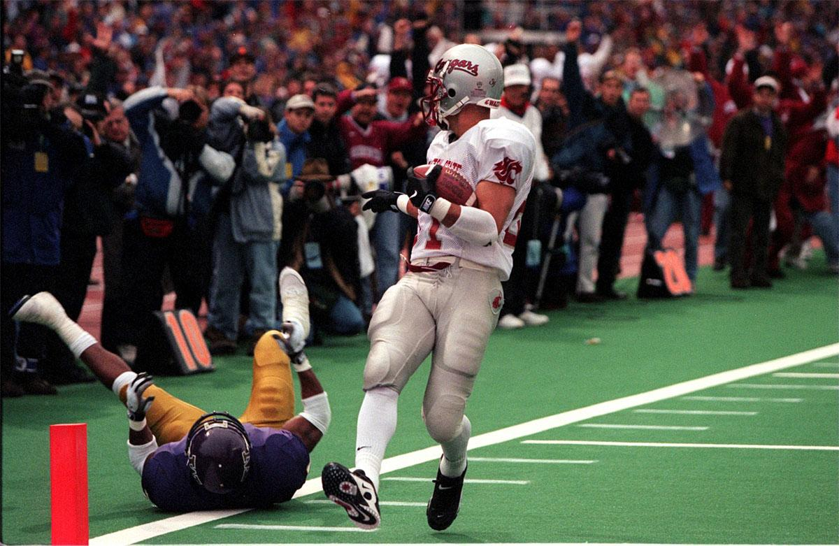 FILE - In this Nov. 22, 1997, file photo, Washington State's Chris Jackson, right, celebrates his touchdown with a taunt over a fallen Washington defender in the Apple Cup NCAA college football game, in Seattle. Twenty years ago, the senior-laden upstart team from Washington State erased 67 years of hardship with one magical season that ended with the school's first Rose Bowl berth since before World War II. The clincher came on a dreary November day in Seattle that concluded with those in crimson and gray storming the turf of Husky Stadium and celebrating an Apple Cup victory over the Huskies. (Mark Harrison/The Seattle Times via AP, File)