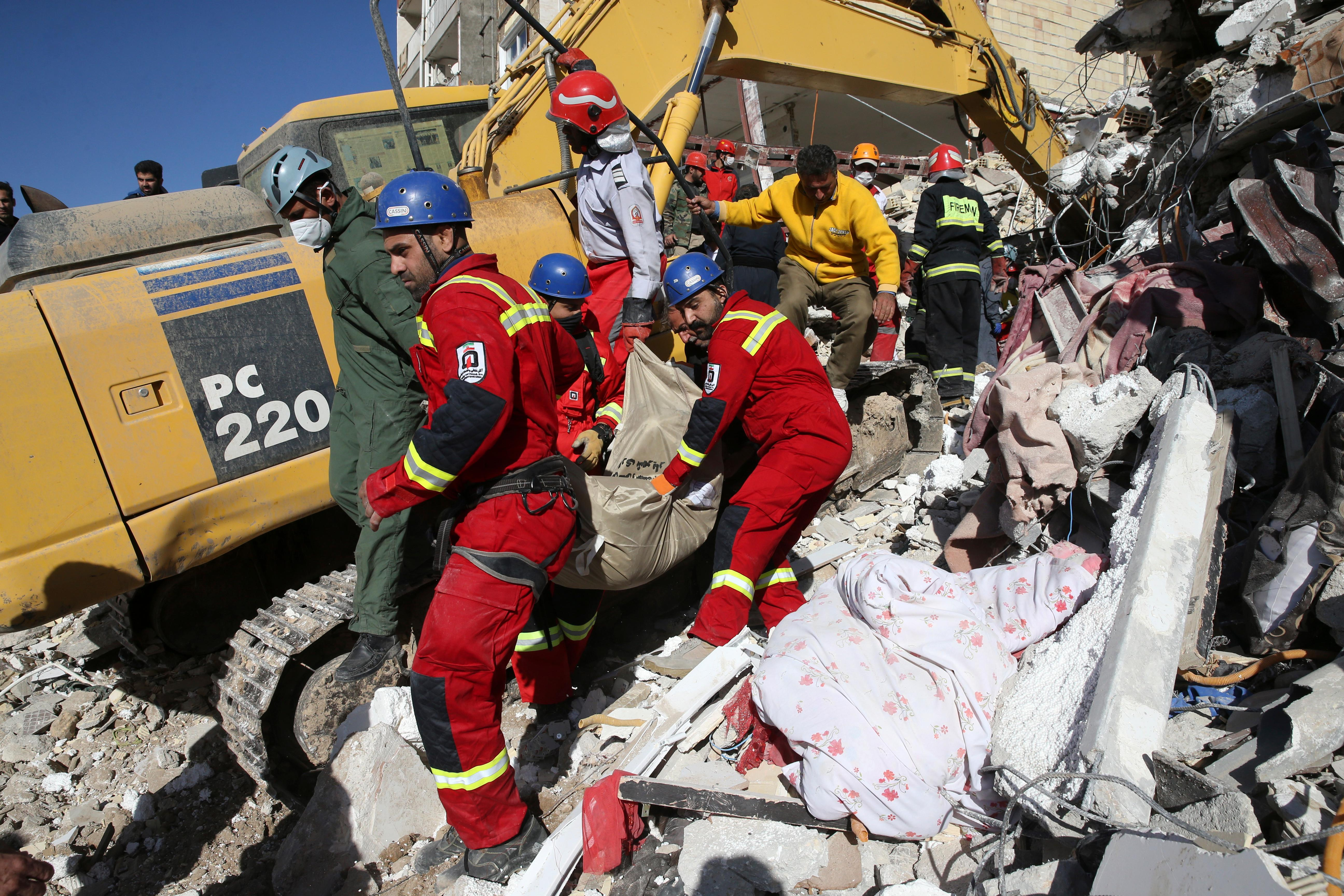 Rescuers carry away the body of an earthquake victim in Sarpol-e-Zahab in western Iran, Tuesday, Nov. 14, 2017. Rescuers are digging through the debris of buildings felled by the Sunday earthquake that killed more than four hundreds of people in the border region of Iran and Iraq. (AP Photo/Vahid Salemi)
