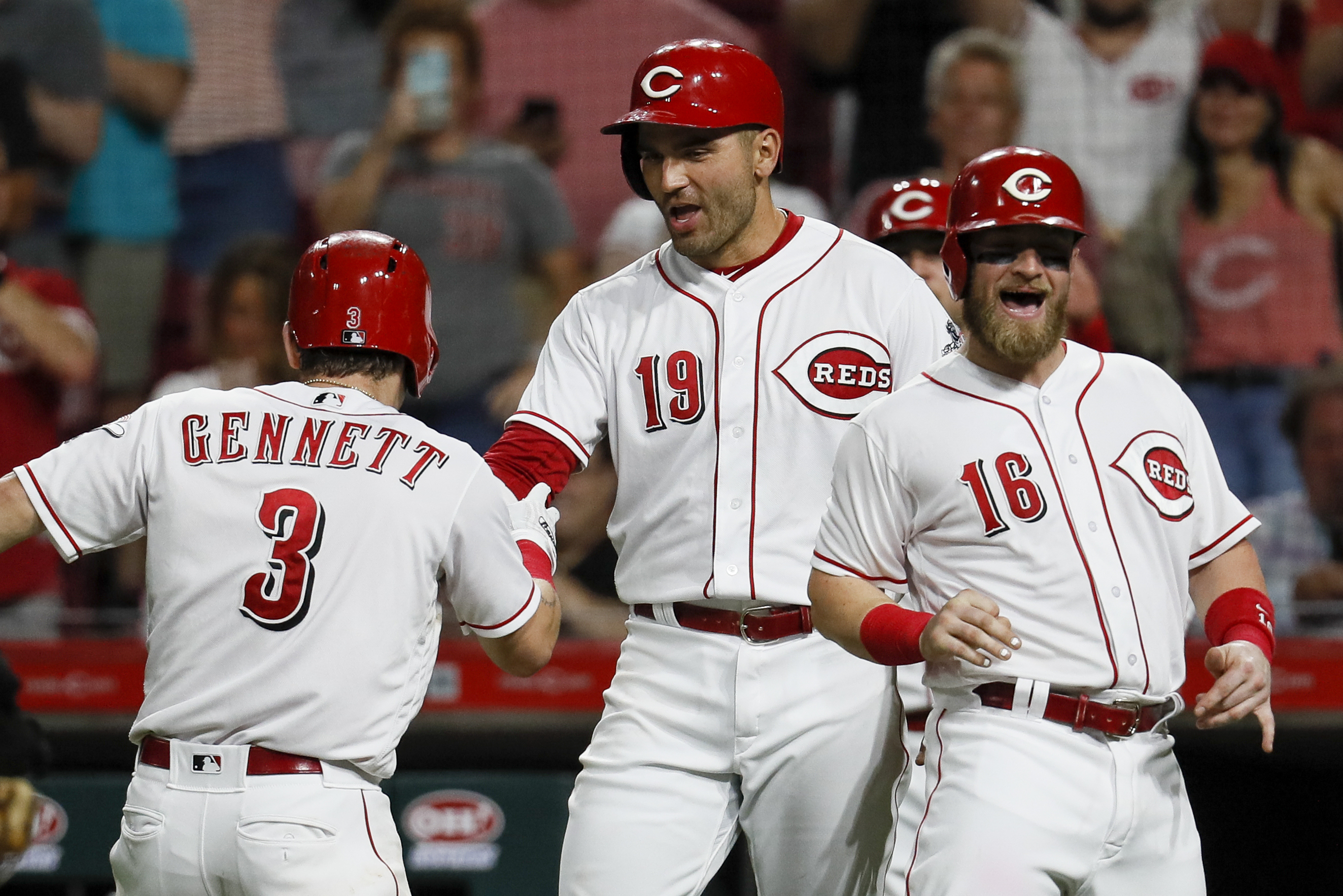 Cincinnati Reds' Scooter Gennett (3) celebrates his grand slam off Pittsburgh Pirates starting pitcher Jameson Taillon with Joey Votto (19) and Tucker Barnhart (16) during the fifth inning of a baseball game Tuesday, May 22, 2018, in Cincinnati. (AP Photo/John Minchillo)