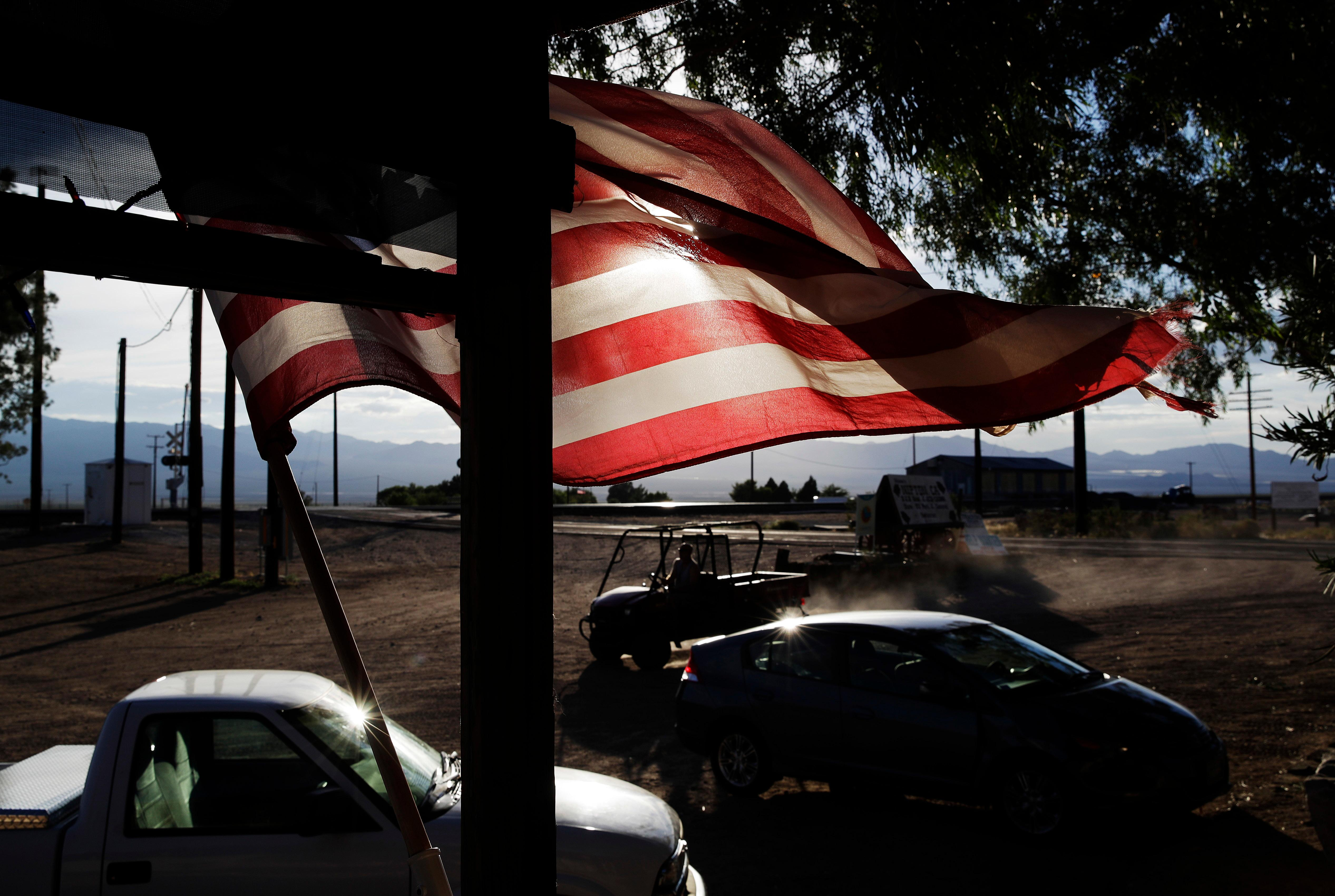 A flag flies in front of a store, Thursday, Aug. 3, 2017, in Nipton, Calif. American Green Inc., one of the nation's largest cannabis companies, announced it has bought the entire 80 acre California desert town of Nipton. (AP Photo/John Locher)
