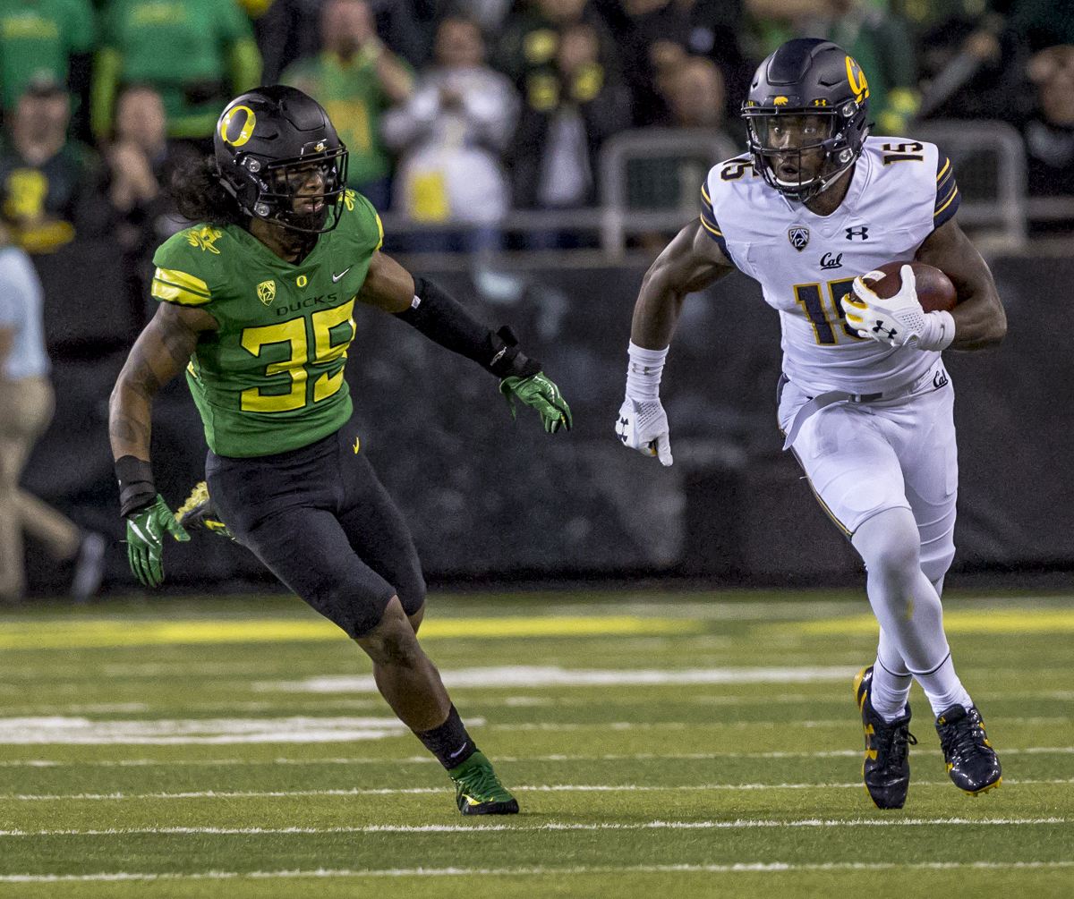 California wide receiver Jordan Veasy (#15) attempts to dodge Oregon defensive player Kaulana Apelu (#39). The Oregon Ducks lead the California Golden Bears 17 to 7 at the end of the first half at Autzen Stadium in Eugene, Ore. Photo by Ben Lonergan, Oregon News Lab