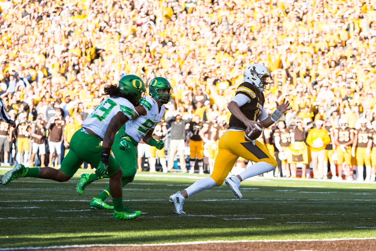 Wyoming quarterback Josh Allen (#17) runs away from two Oregon defenders for a touchdown.  The Oregon Ducks lead the Wyoming Cowboys 42 to 10 at the end of the first half on Saturday, September 16, 2017 in Laramie, Wyo. Photo by Austin Hicks, Oregon News Lab