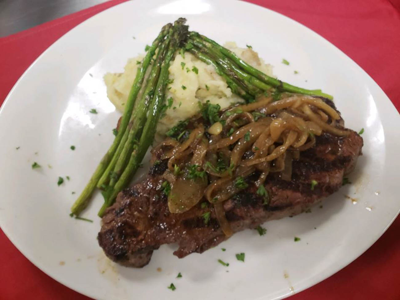 <p>FIRE's New York Strip: 12 oz. center cut, buttermilk crushed Yukon potatoes, garlic green beans, and crisp cumin onion / Image courtesy of RiverCenter Entertainment // Published: 6.20.19</p>