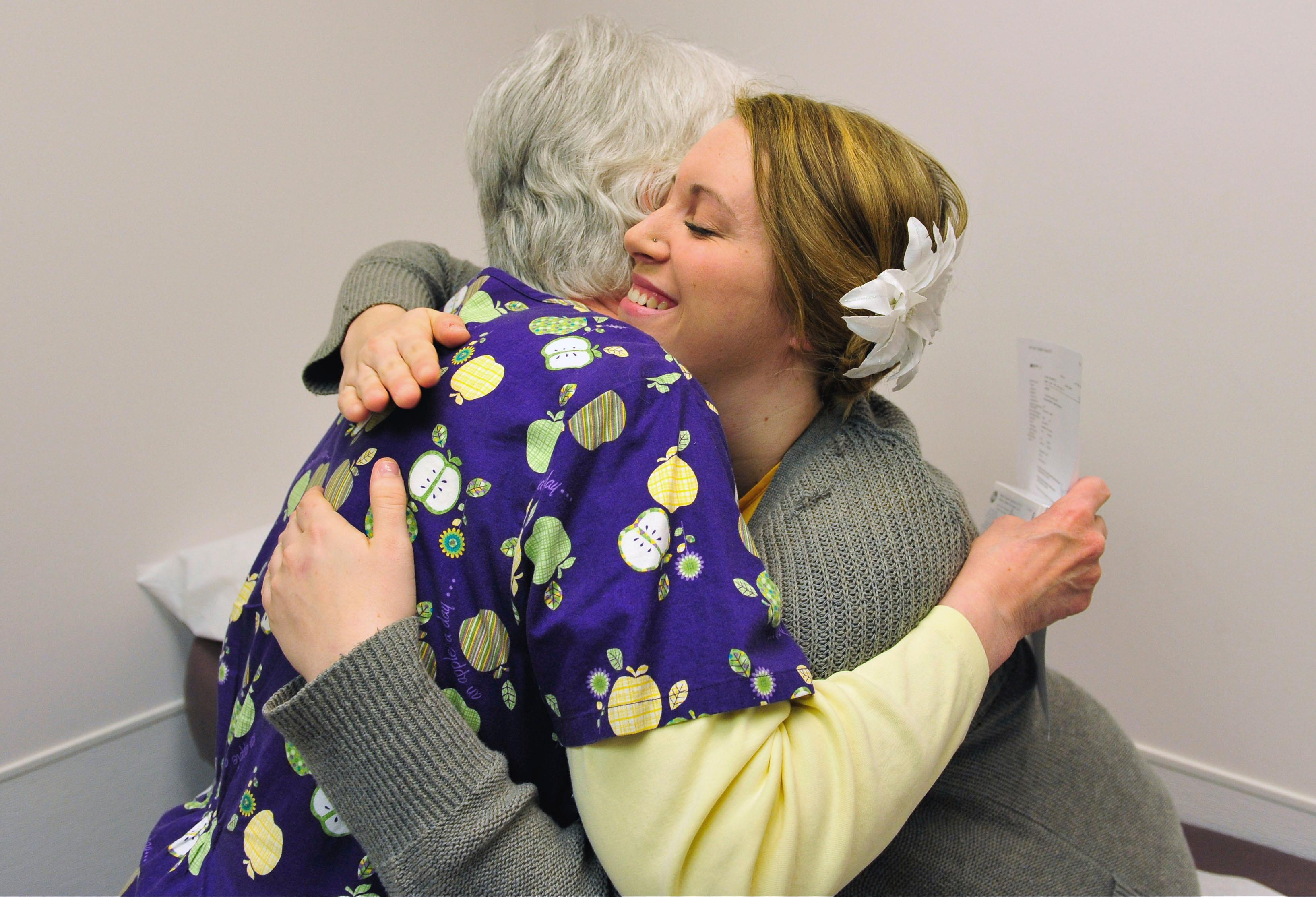Pharmacist Kathie Gasper hugs patient Heidi Wyandt, 27, after receiving an injection as part of an experimental non-opioid pain medication trial at the Altoona Center for Clinical Research in Altoona, Pa., on Wednesday, March 29, 2017. Wyandt has chronic back pain related to a work related injury she received in 2014. With about 2 million Americans hooked on opioid painkillers, researchers and drug companies are searching for less addictive drugs to treat pain. (AP Photo/Chris Post)