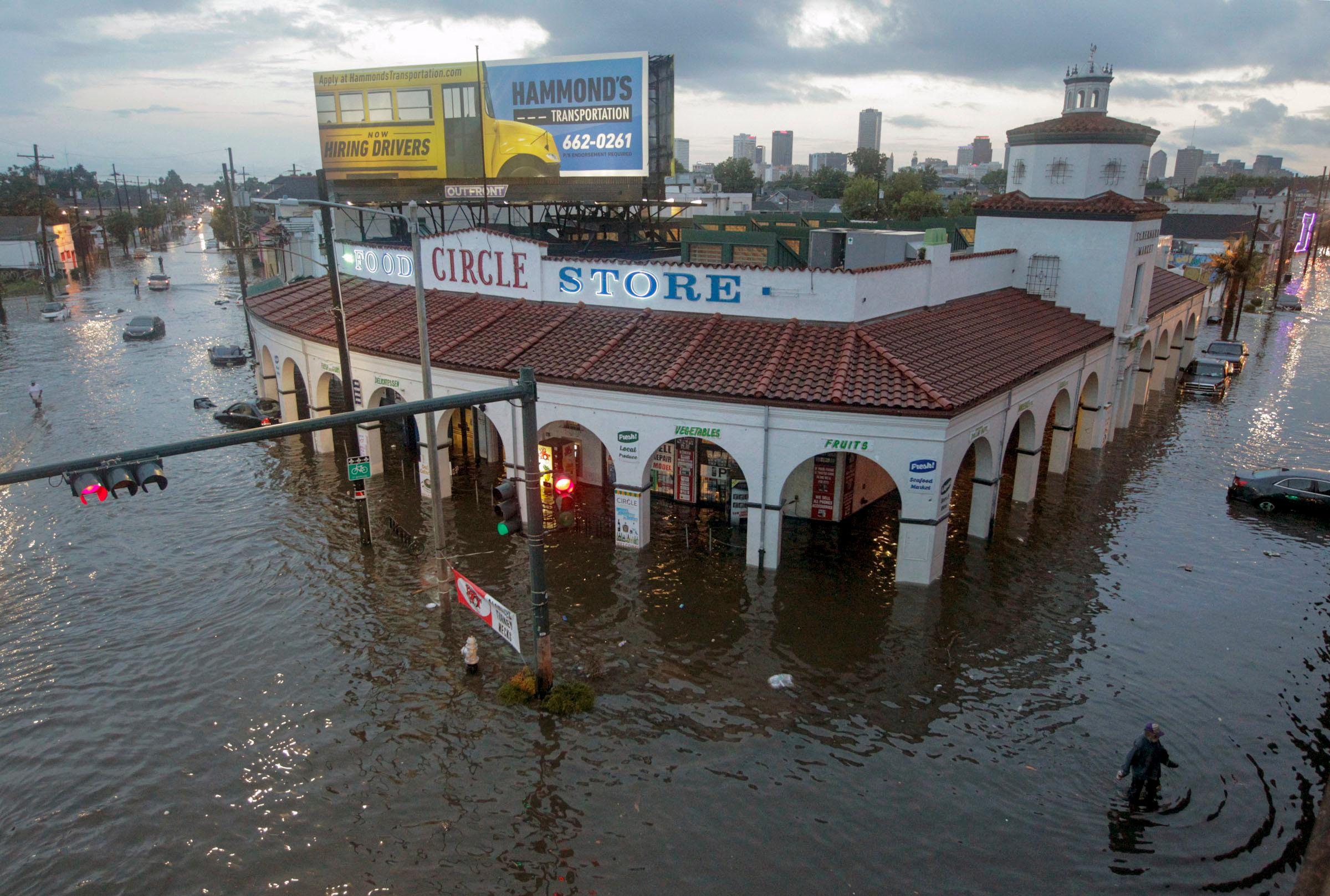 FILE - This Saturday, Aug. 5, 2017, file photo shows the Circle Food Store engulfed in floodwaters in New Orleans. With more rain in the forecast and city water pumps malfunctioning after weekend floods, New Orleans' mayor is urging residents of some waterlogged neighborhoods to move their vehicles to higher ground. Mayor Mitch Landrieu's office said early Thursday, Aug. 10, 2017, the city has lost service to one of its power turbines, which powers most of the pumping stations service the East Bank of New Orleans. (Brett Duke/NOLA.com The Times-Picayune via AP, File)