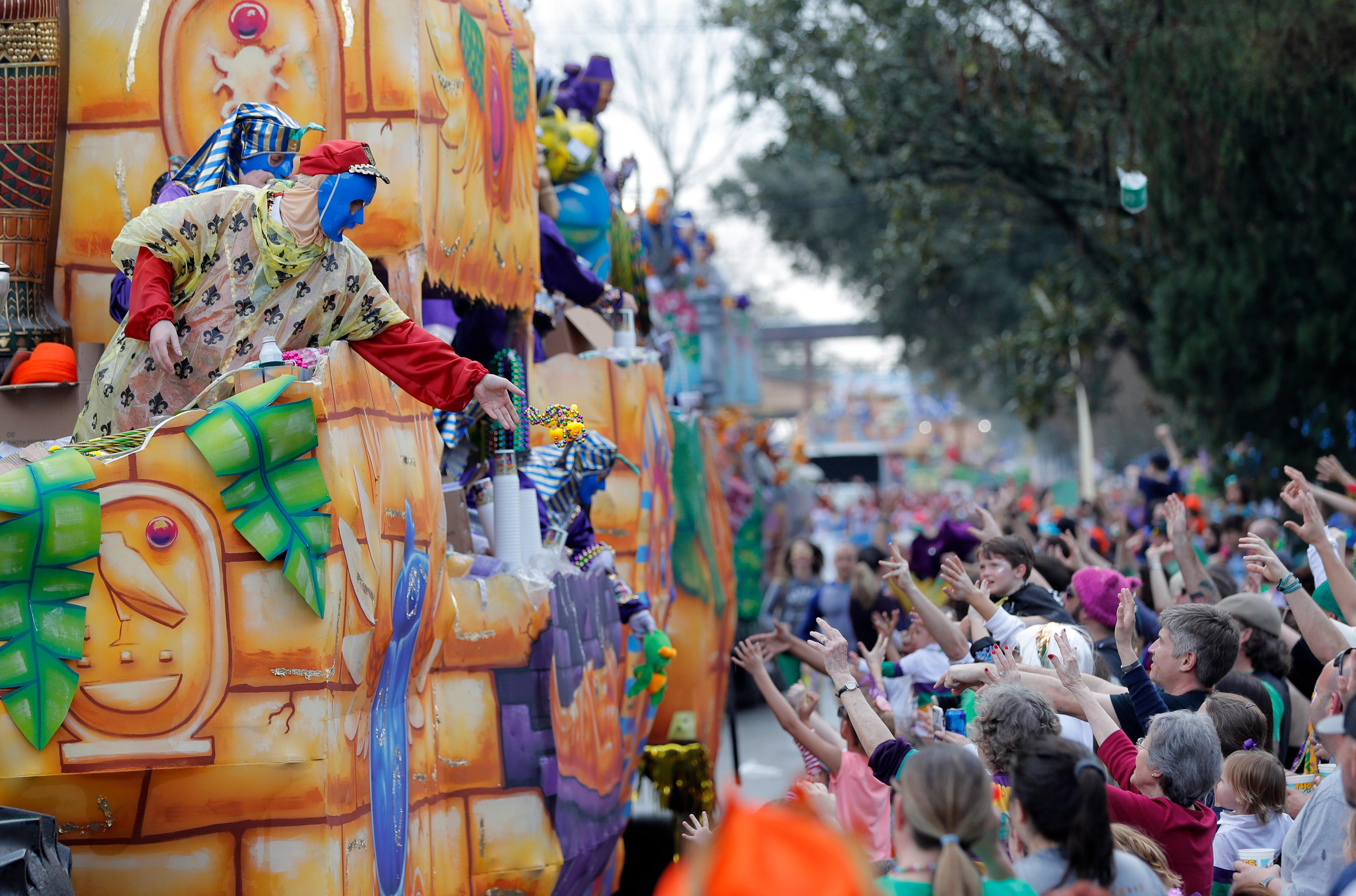 Float riders toss beads and trinkets during the Krewe of Thoth Mardi Gras parade in New Orleans, Sunday, Feb. 11, 2018. The krewe's original parade route was designed specifically to serve people who were unable to attend other parades in the city. The route passes in front of several extended healthcare facilities. Carnival season will culminate on Mardi Gras day this Tuesday, Feb. 13. (AP Photo/Gerald Herbert)