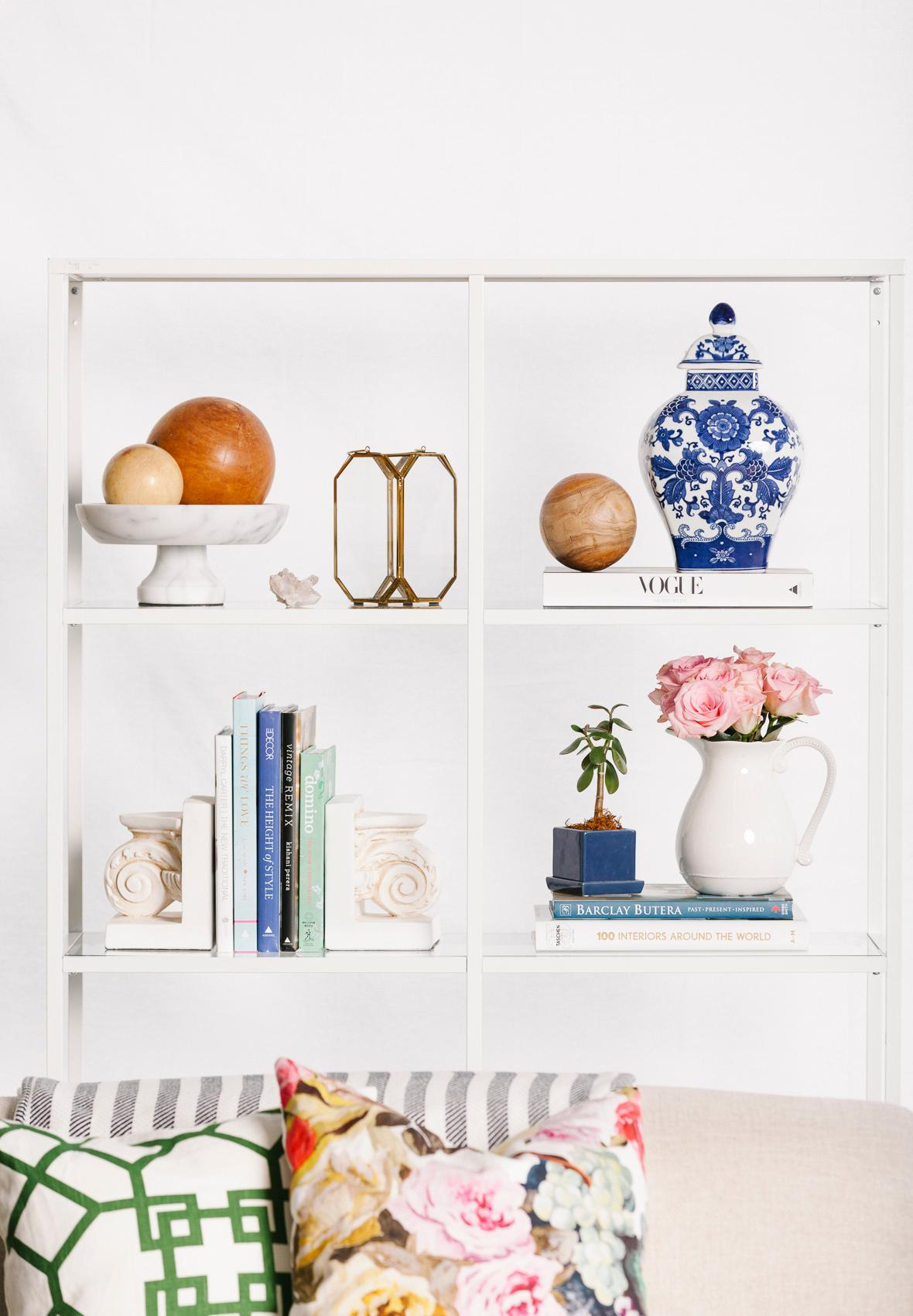 All white shelving with pops of color is perfect for a posh, feminine living room. (Image: Courtesy Havenly)