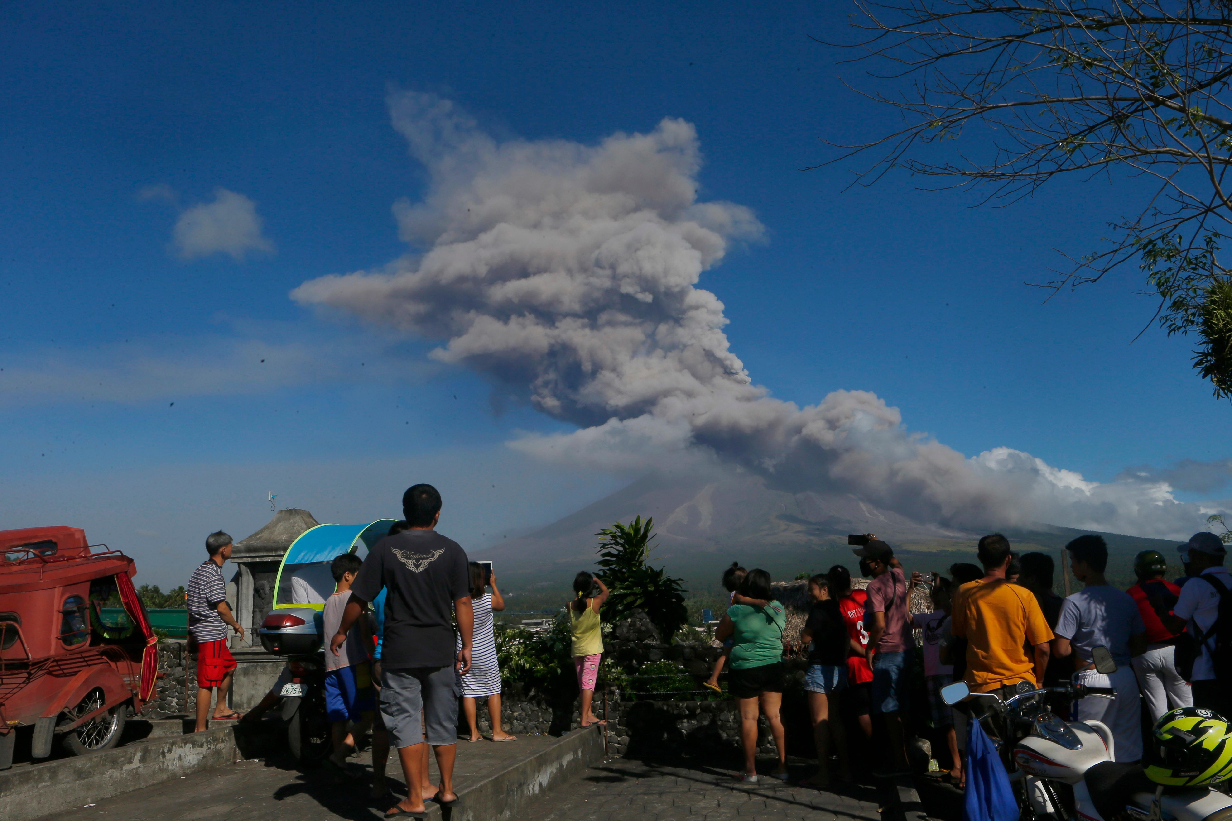 Residents watch as Mayon volcano spews ash anew during its eruption for the second straight day Tuesday, Jan. 23, 2018 as seen from Legazpi city, Albay province, southeast of Manila, Philippines. The Philippines' most active volcano ejected a huge column of lava fragments, ash and smoke in another thunderous explosion at dawn Tuesday, sending thousands of villagers back to evacuation centers and prompting a warning that a violent eruption may be imminent. (AP Photo/Bullit Marquez)
