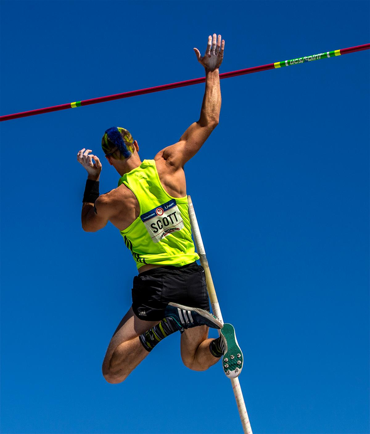 Jordan Scott shows off both his blue and green styled haircut and his pole vaulting skills as he clears the bar. Photo by August Frank, Oregon News Lab