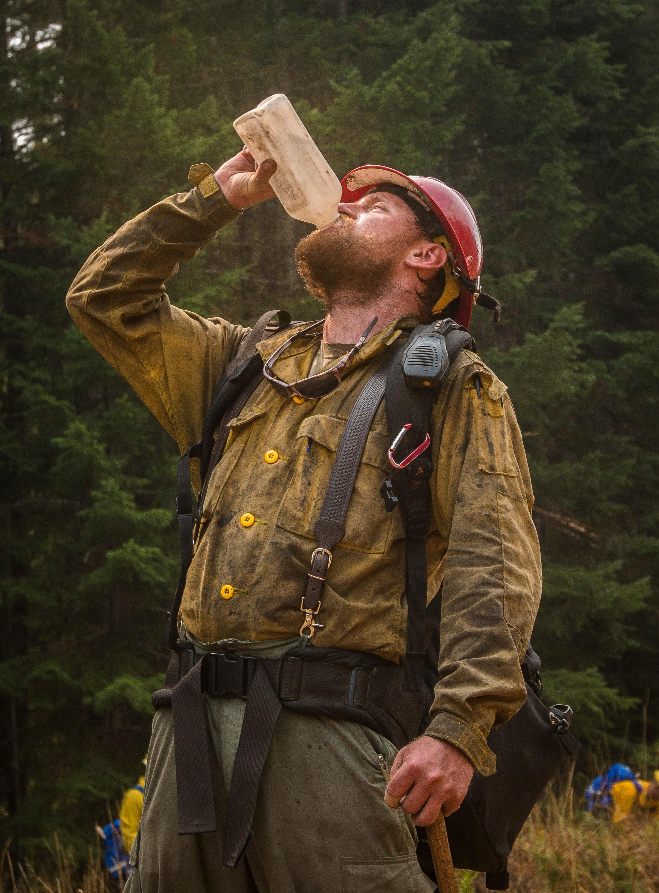 Zane Willert, a firefighter with the Devil's Canyon Handcrew, stays hydrated while supervising tactical training with the Soldiers assigned to 23rd Brigade Engineer Battalion, 1-2 Stryker Brigade Combat Team, Umpqua North Complex, Oregon, Sept. 8. When not fighting the flames during wildfire season, Willert is a cattle rancher in Wyoming. (U.S. Army photo by Pvt. Adeline Witherspoon, 20th Public Affairs Detachment)