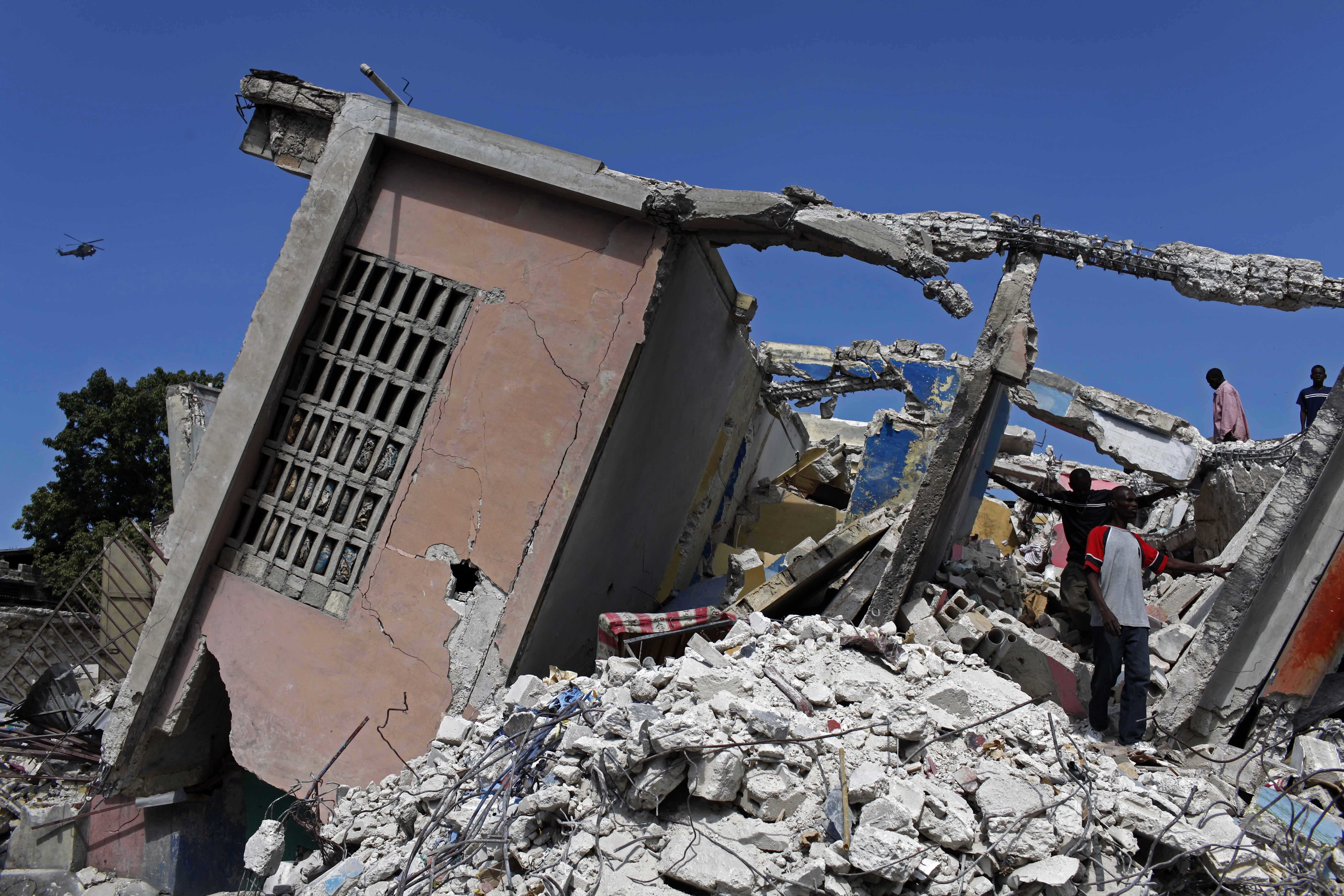 FILE - In this Jan. 30, 2010, file photo, people stand in the rubble of a collapsed building in the aftermath of a massive earthquake in Port-au-Prince. The Trump administration is hunting for evidence of crimes committed by Haitian immigrants as it decides whether to allow them to continue participating in a humanitarian program that has shielded tens of thousands from deportation since the 2010 earthquake. The Homeland Security Department has not made a final decision about Temporary Protected Status for Haiti and declined to comment on the pre-decisional process. The Obama administration included Haiti in the program shortly after the January 2010 earthquake that killed as many as 300,000 people and devastated schools, hospitals, homes and even entire neighborhoods (AP Photo/Rodrigo And, File)
