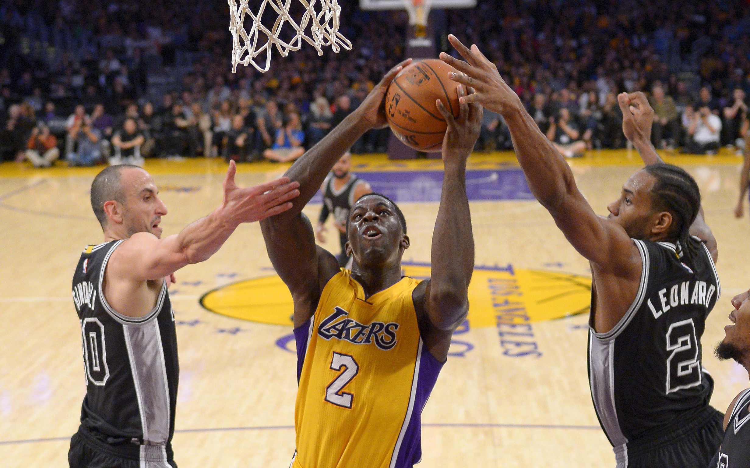 Los Angeles Lakers forward Brandon Bass shoots between San Antonio Spurs guard Manu Ginobili, left, and forward Kawhi Leonard during the first half of an NBA basketball game Friday, Jan. 22, 2016, in Los Angeles. (AP Photo/Mark J. Terrill)