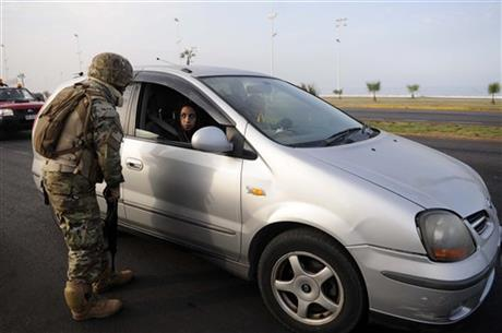 A Chilean soldier inspects a car in the northern town of Iquique, Chile, after magnitude 8.2 earthqauke struck the northen coast of Chile, Wednesday, April 2, 2014.