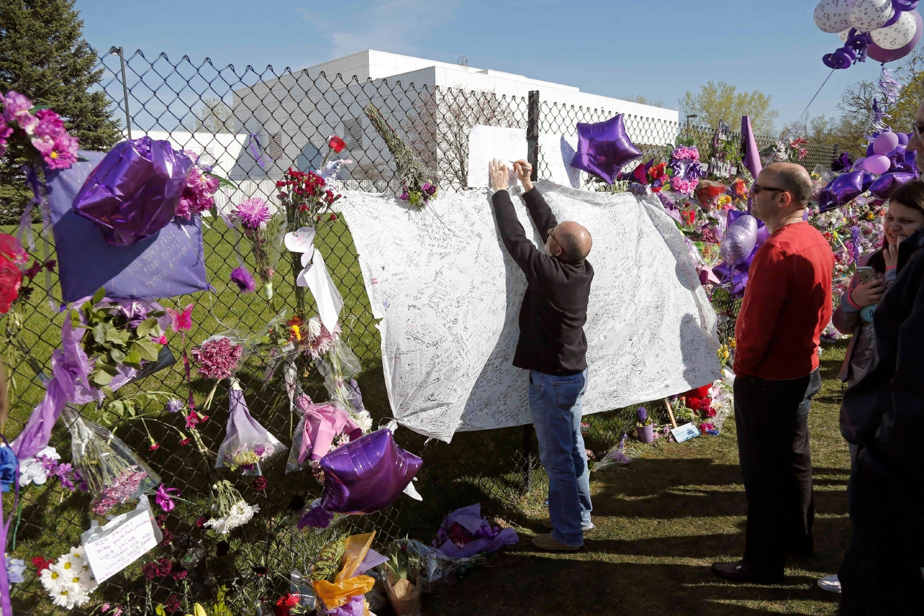 A fan writes a note at the memorial fence in memory of pop star Prince at Paisley Park Studios Friday, April 22, 2016 in Chanhassen, Minn. Prince died Thursday at Paisley Park at the age of 57. (AP Photo/Jim Mone)