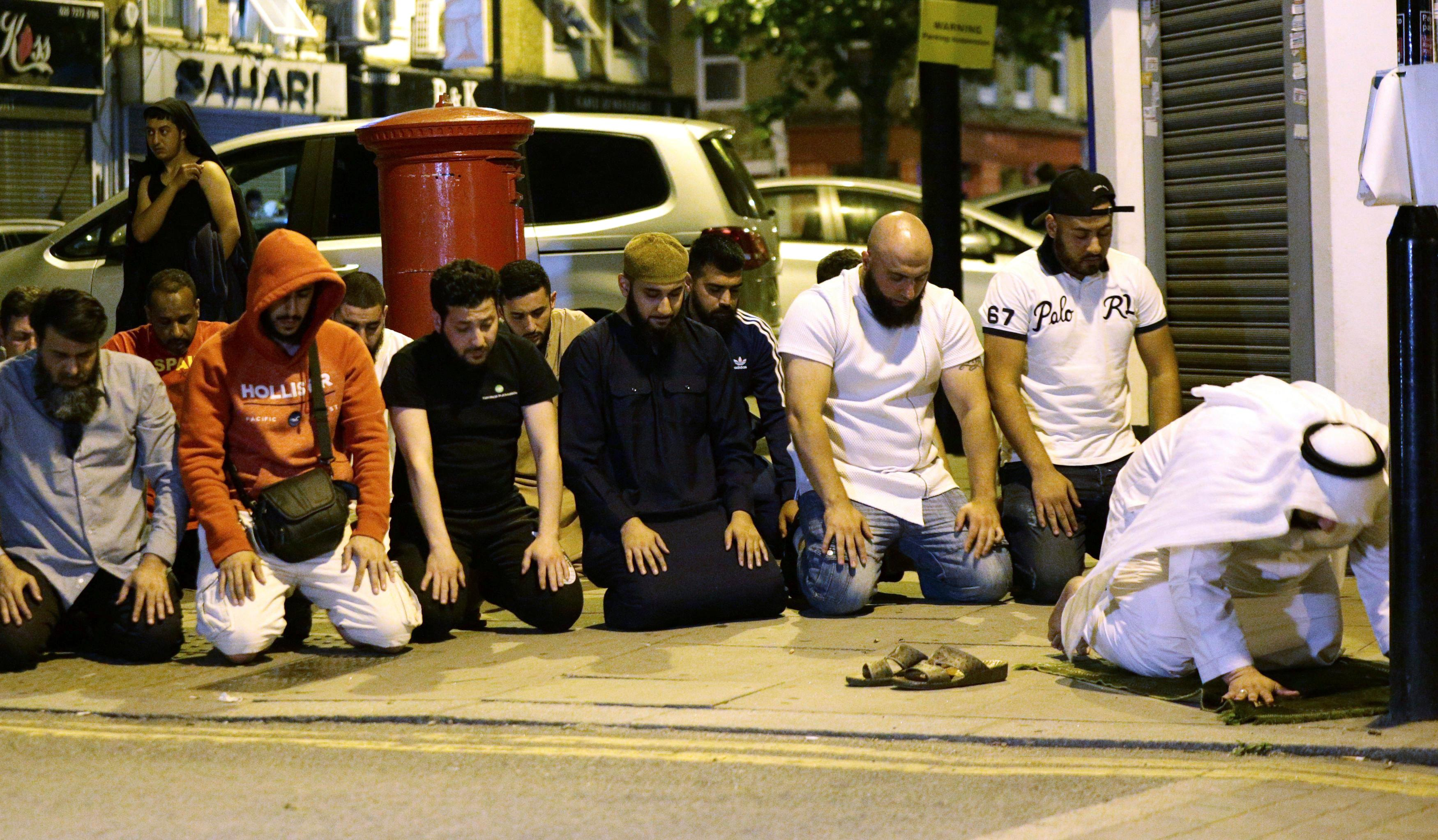 Local people observe prayers at Finsbury Park where a vehicle struck pedestrians in London Monday, June 19, 2017. Police say a vehicle struck pedestrians near a mosque in north London, leaving several casualties and one person was arrested. (Yui Mok/PA via AP)