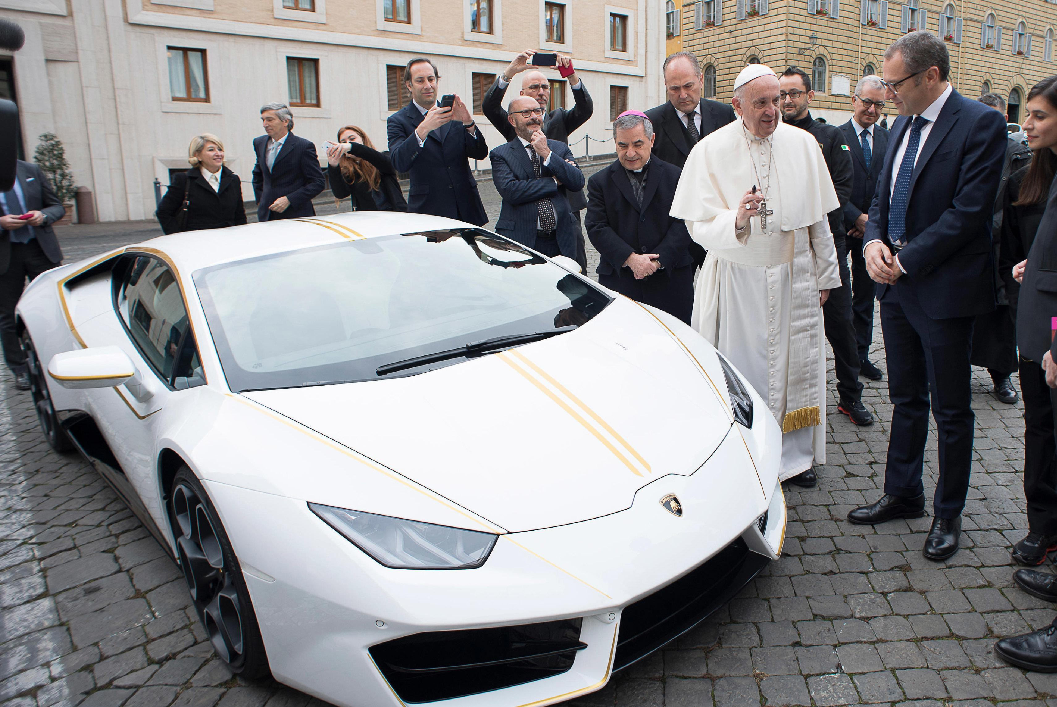 Pope Francis speaks with CEO of Lamborghini Stefano Domenicali next to a white Lamborghini donated to the pontiff by the luxury sports car maker, at the Vatican, Wednesday, Nov. 15, 2017. The car will be auctioned off by Sotheby's, with the proceeds going to charities including one aimed at helping rebuild Christian communities in Iraq that were devastated by the Islamic State group. (L'Osservatore Romano/Pool Photo via AP)
