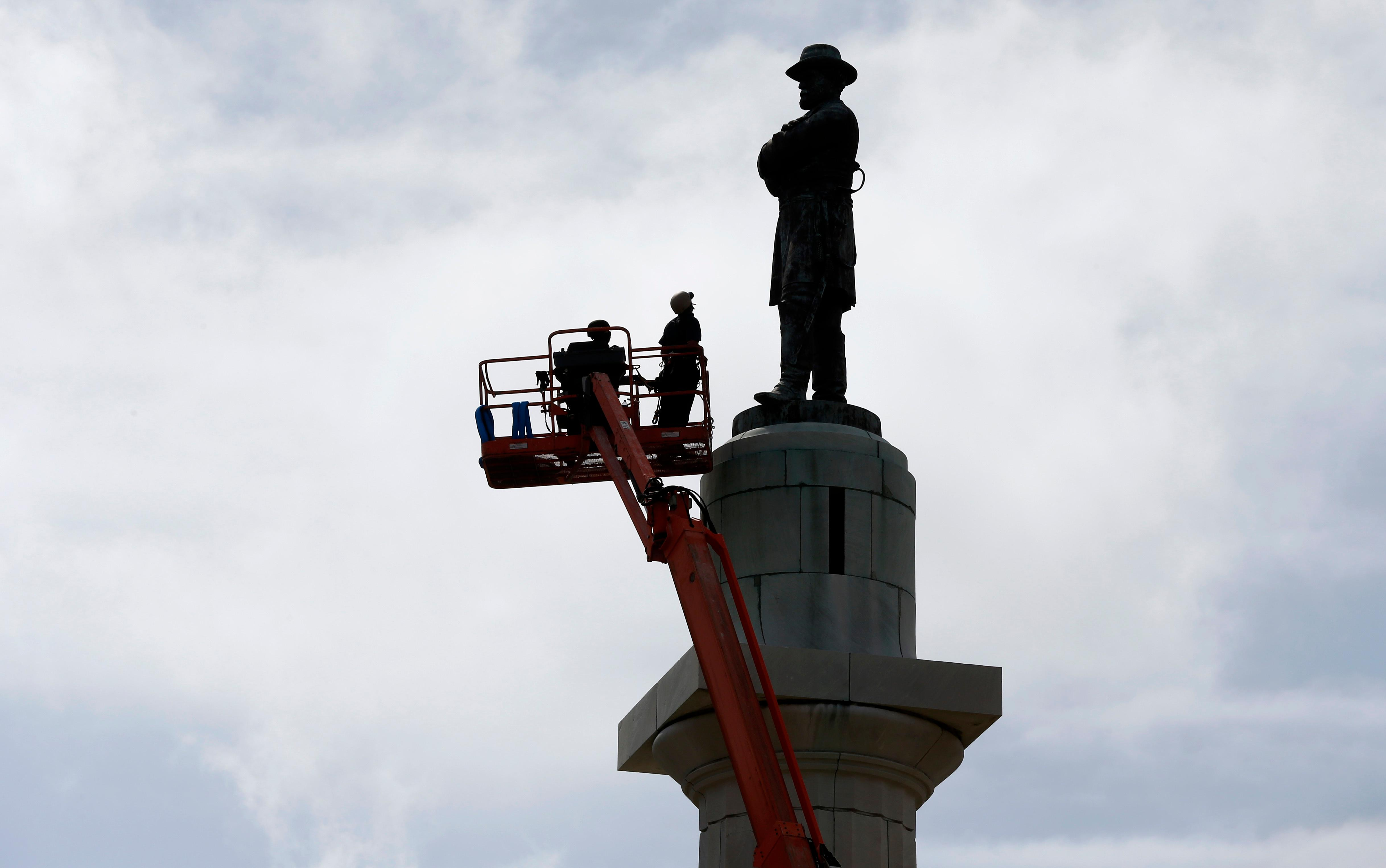 CORRECTS TITLE FROM PRESIDENT TO GENERAL Workers prepare to take down the statue of Robert E. Lee, former general of the Confederacy, which stands in Lee Circle in New Orleans, Friday, May 19, 2017.  The city is completing the Southern city's removal of four Confederate-related statues that some called divisive. (AP Photo/Gerald Herbert)