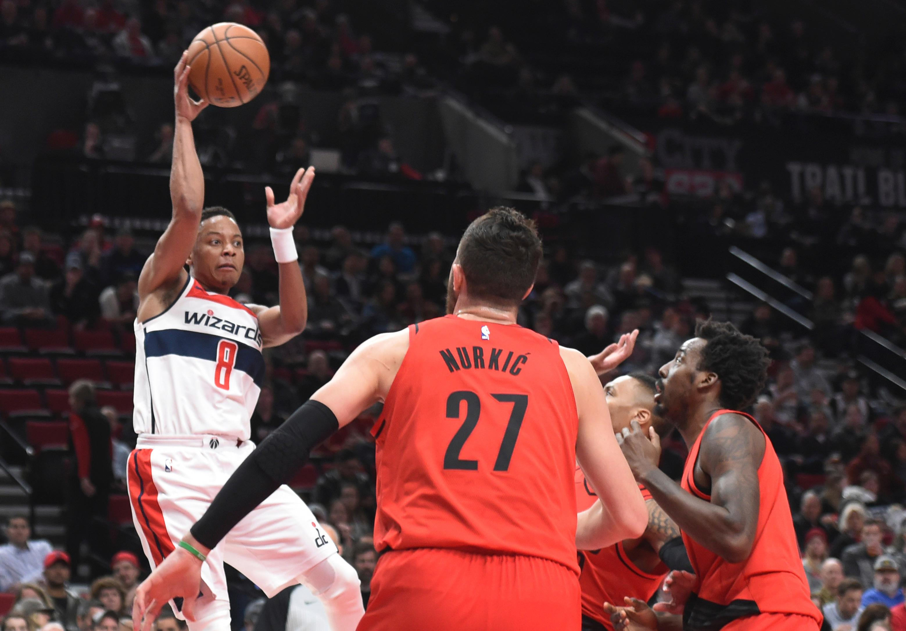 Washington Wizards guard Tim Frazier passes the ball over Portland Trail Blazers center Jusuf Nurkic during the first half of an NBA basketball game in Portland, Ore., Tuesday, Dec. 5, 2017. (AP Photo/Steve Dykes)
