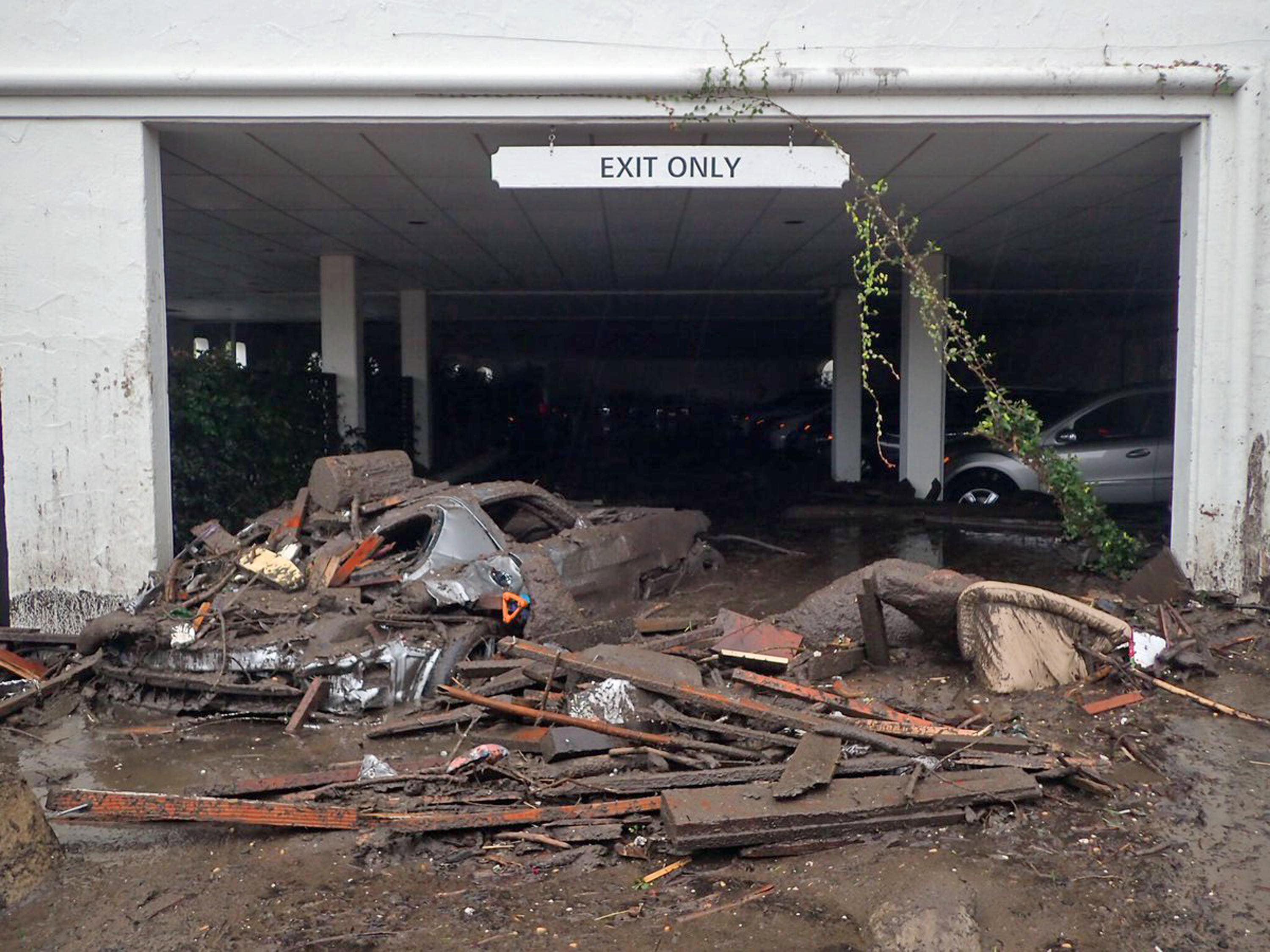 This photo provided by the Santa Barbara County Fire Department shows damaged vehicles carried by mud flow and debris at the parking garage of The Montecito Inn in Montecito, Calif., Tuesday, Jan. 9, 2018. Several homes were swept away before dawn Tuesday when mud and debris roared into neighborhoods in Montecito from hillsides stripped of vegetation during the Thomas wildfire. (Mike Eliason/Santa Barbara County Fire Department via AP)