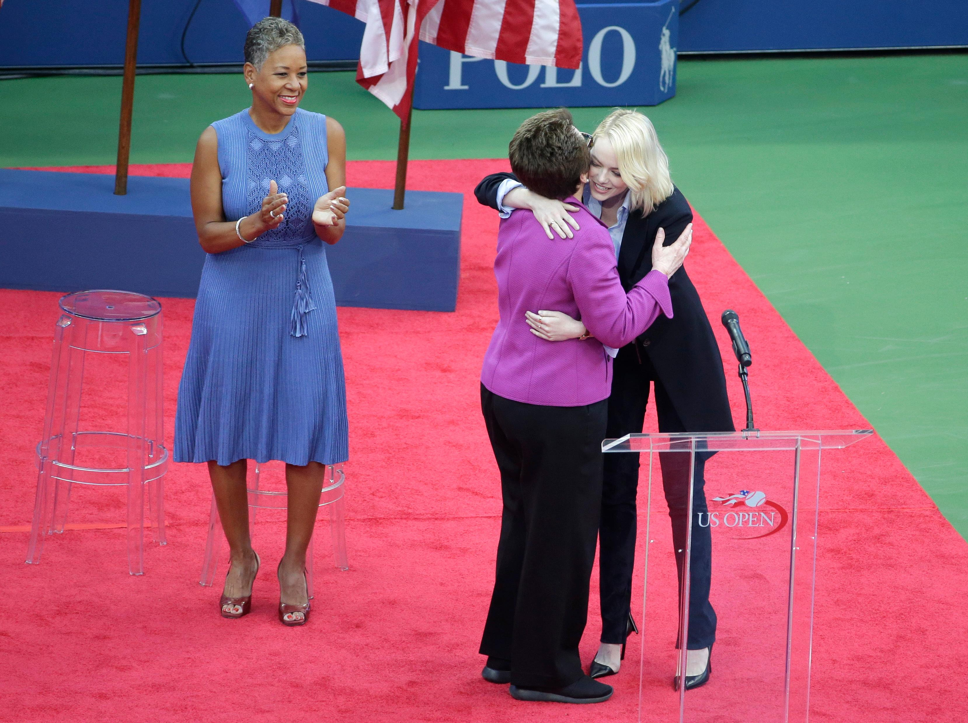 Actress Emma Stone, right, hugs Billie Jean King as USTA CEO Katrina Adams looks on before the start of the women's singles championship match between Sloane Stephens, of the United States, and Madison Keys, of the United States, at the U.S. Open tennis tournament, Saturday, Sept. 9, 2017, in New York. (AP Photo/Seth Wenig)